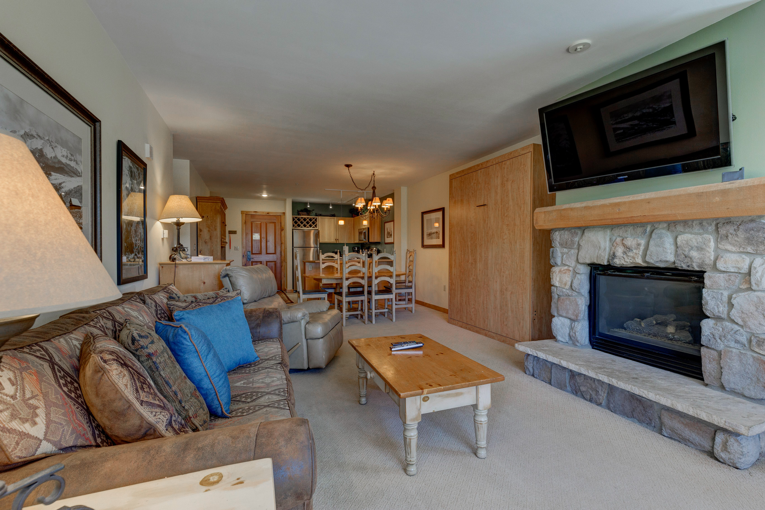 The living area features a mounted flat screen TV, beautiful gas fireplace and queen-sized sleeper sofa.