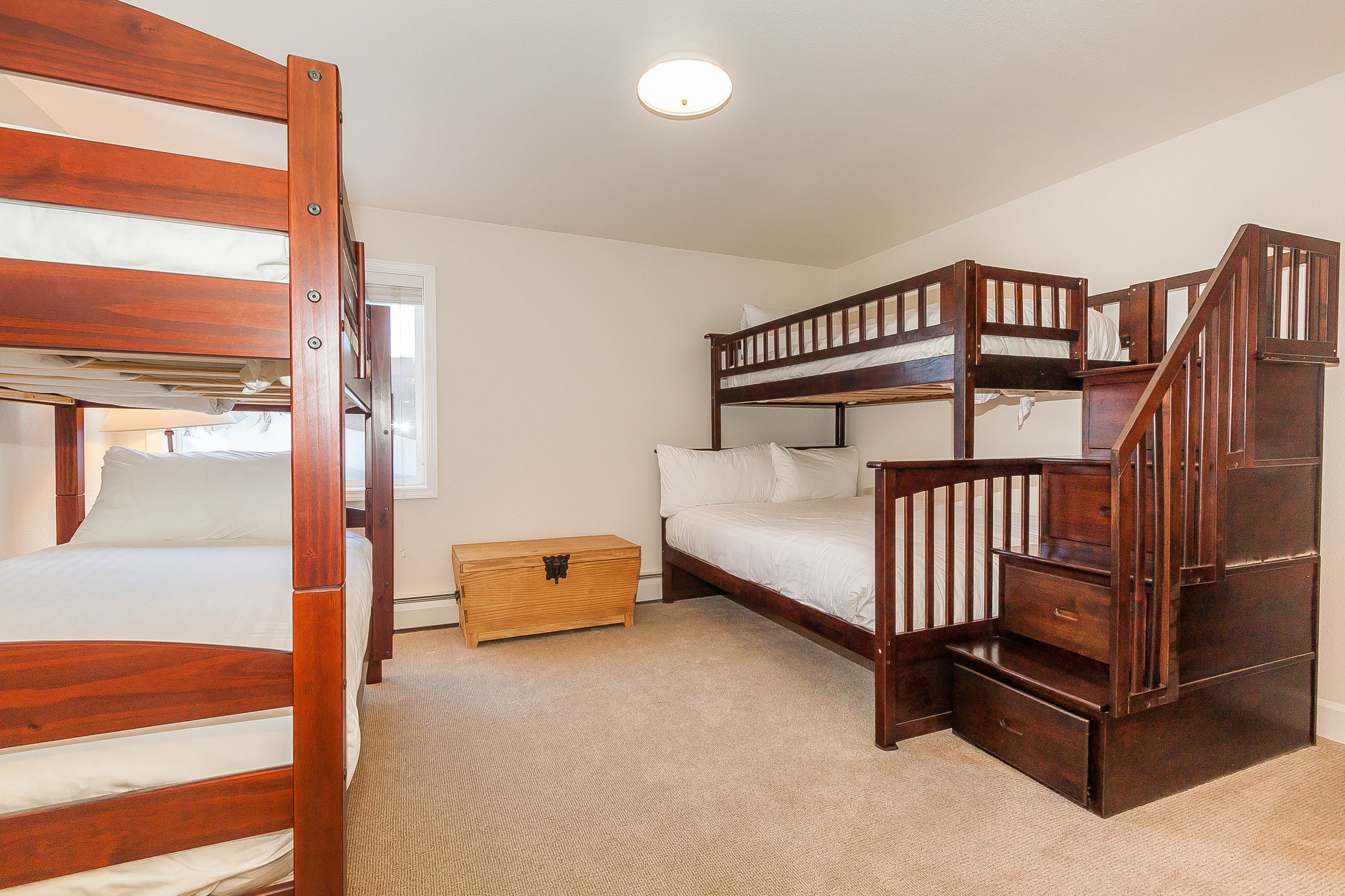 The guest bedroom is downstairs and features a twin-over-full and a twin-sized bunk bed with Ivory White Bedding.
