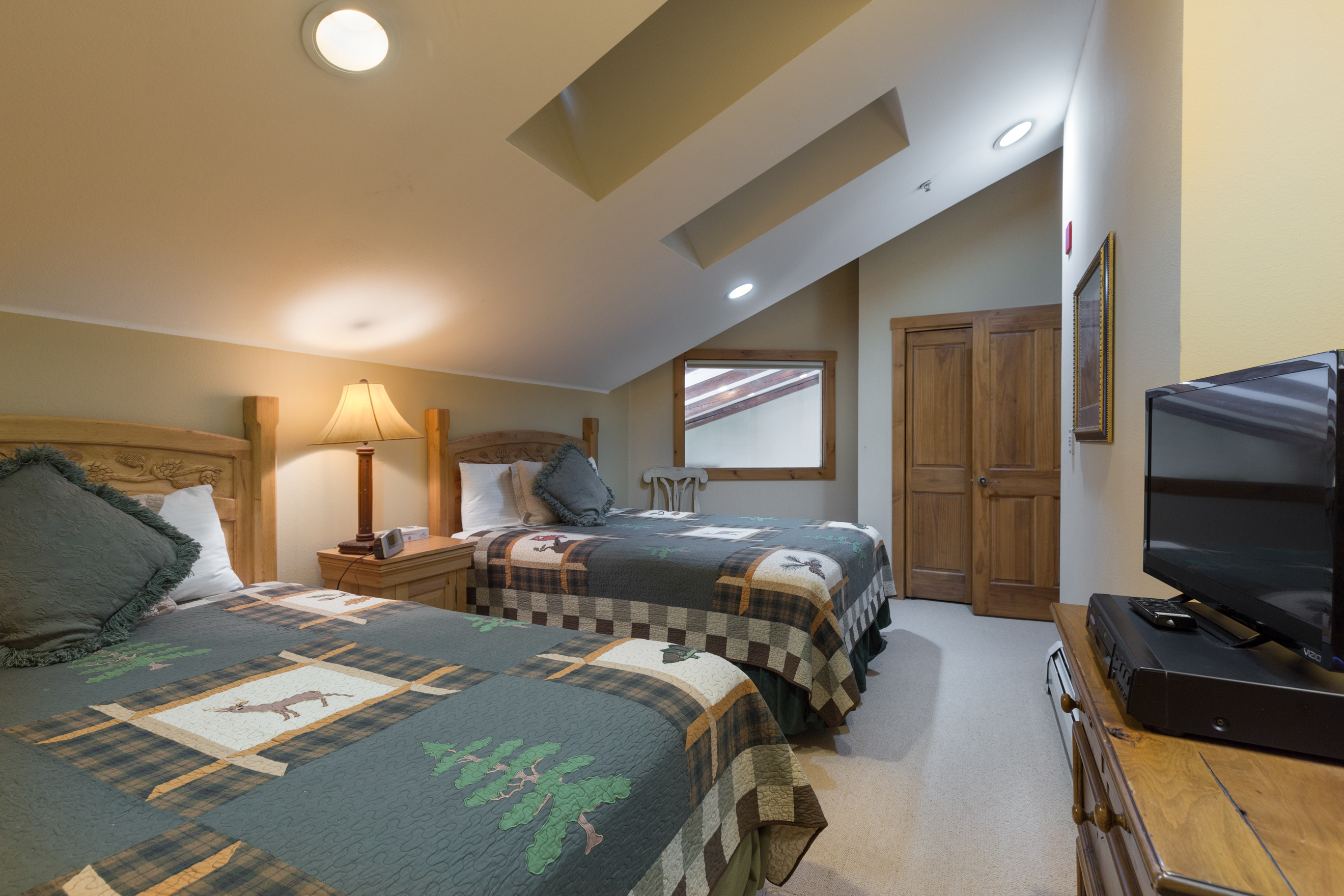 The fifth bedroom upstairs features two queen-sized beds and a flat screen TV as well as skylights.
