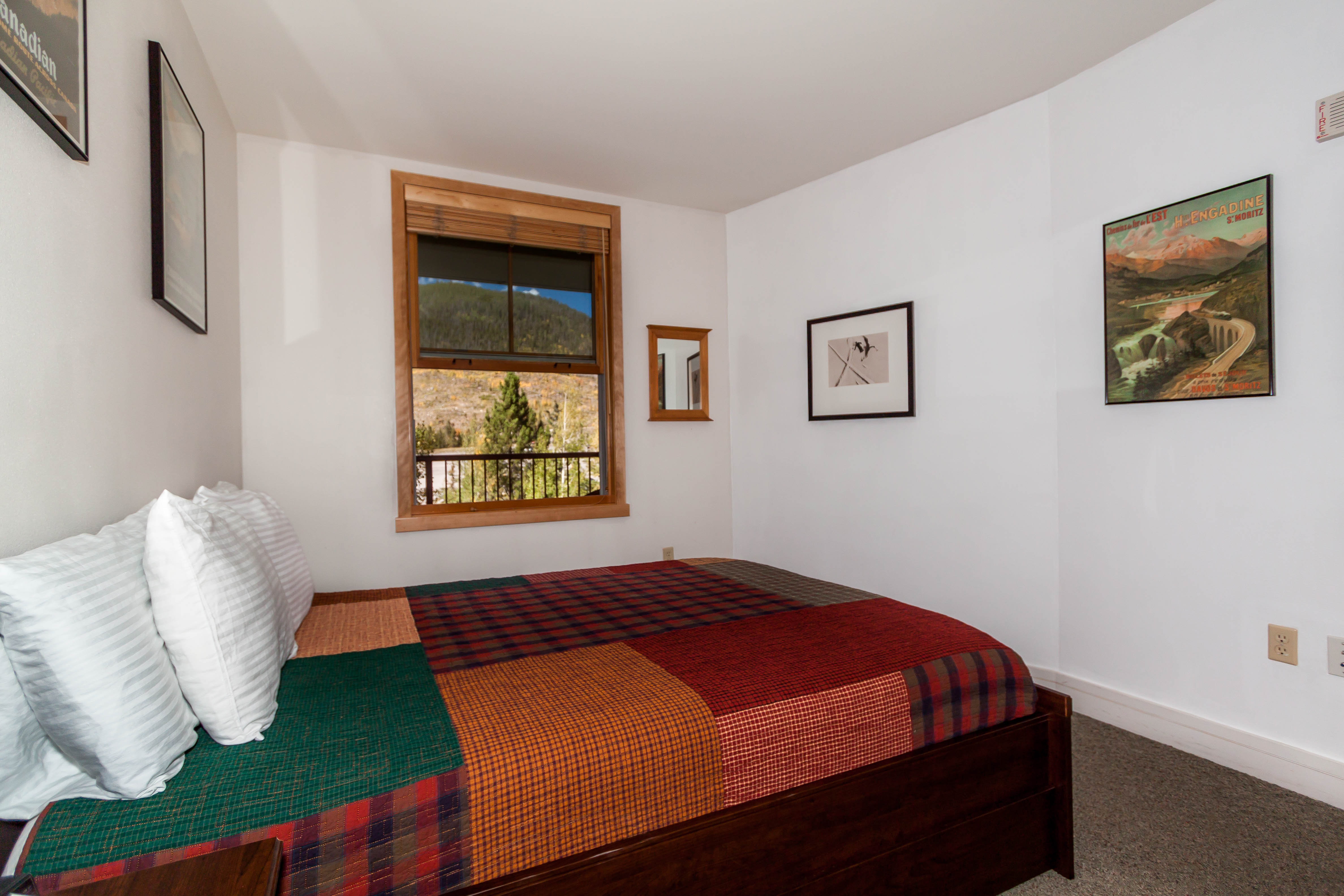 The bedroom features a queen-sized bed and offers mountain views.