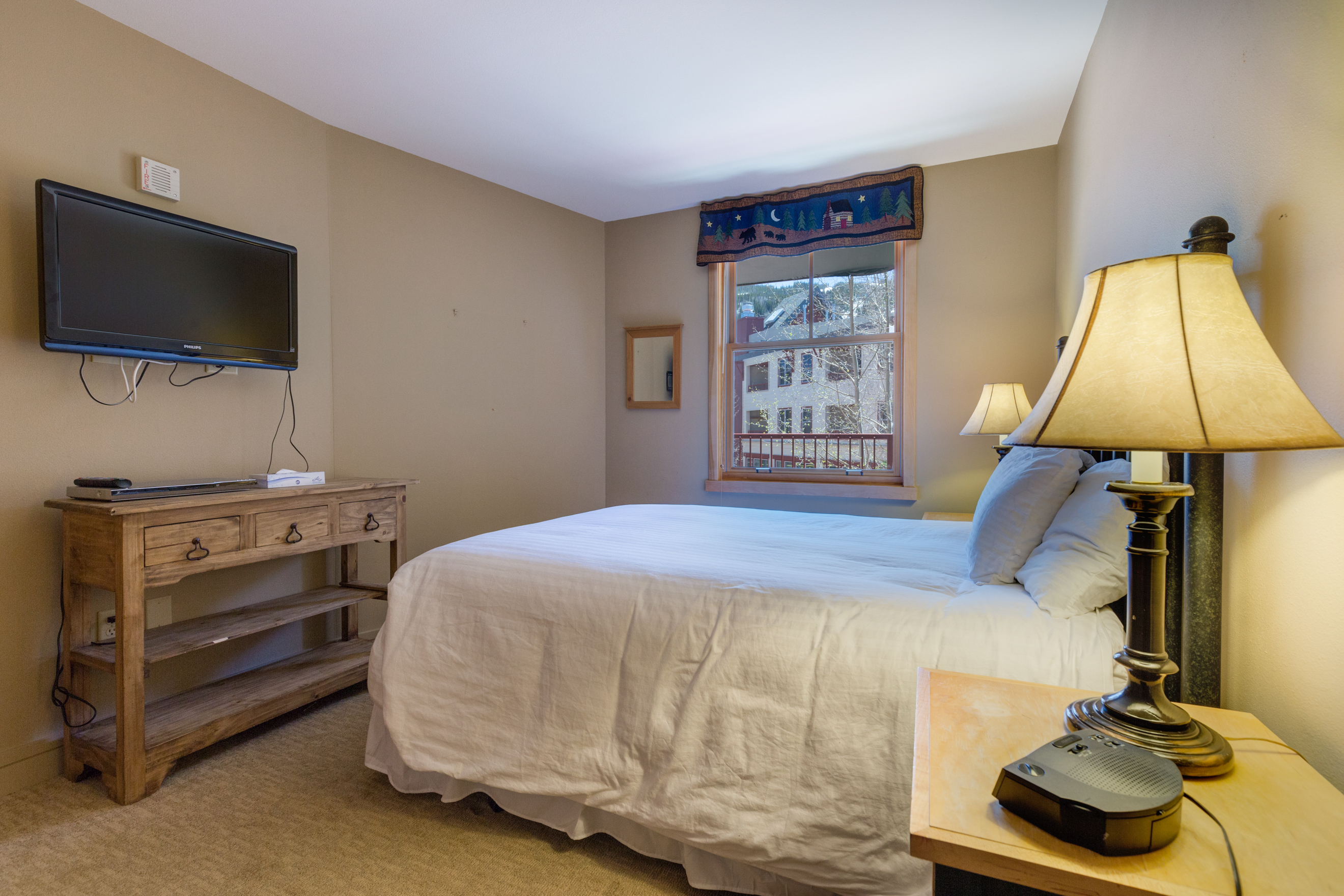 The bedroom features a queen-sized bed Ivory White Bedding and a flat screen TV.