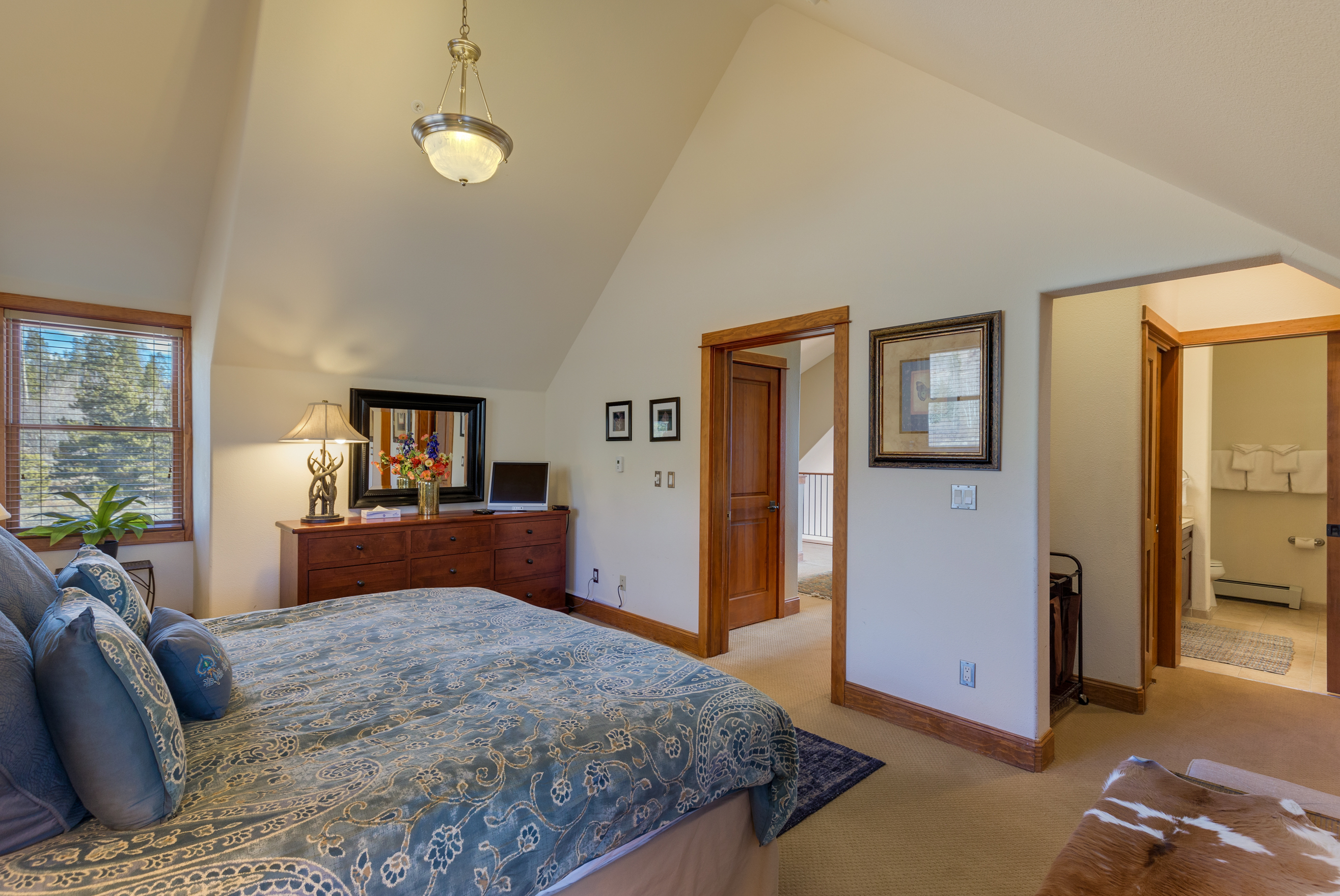 The master bedroom features a king-sized bed, vaulted ceilings and a television.