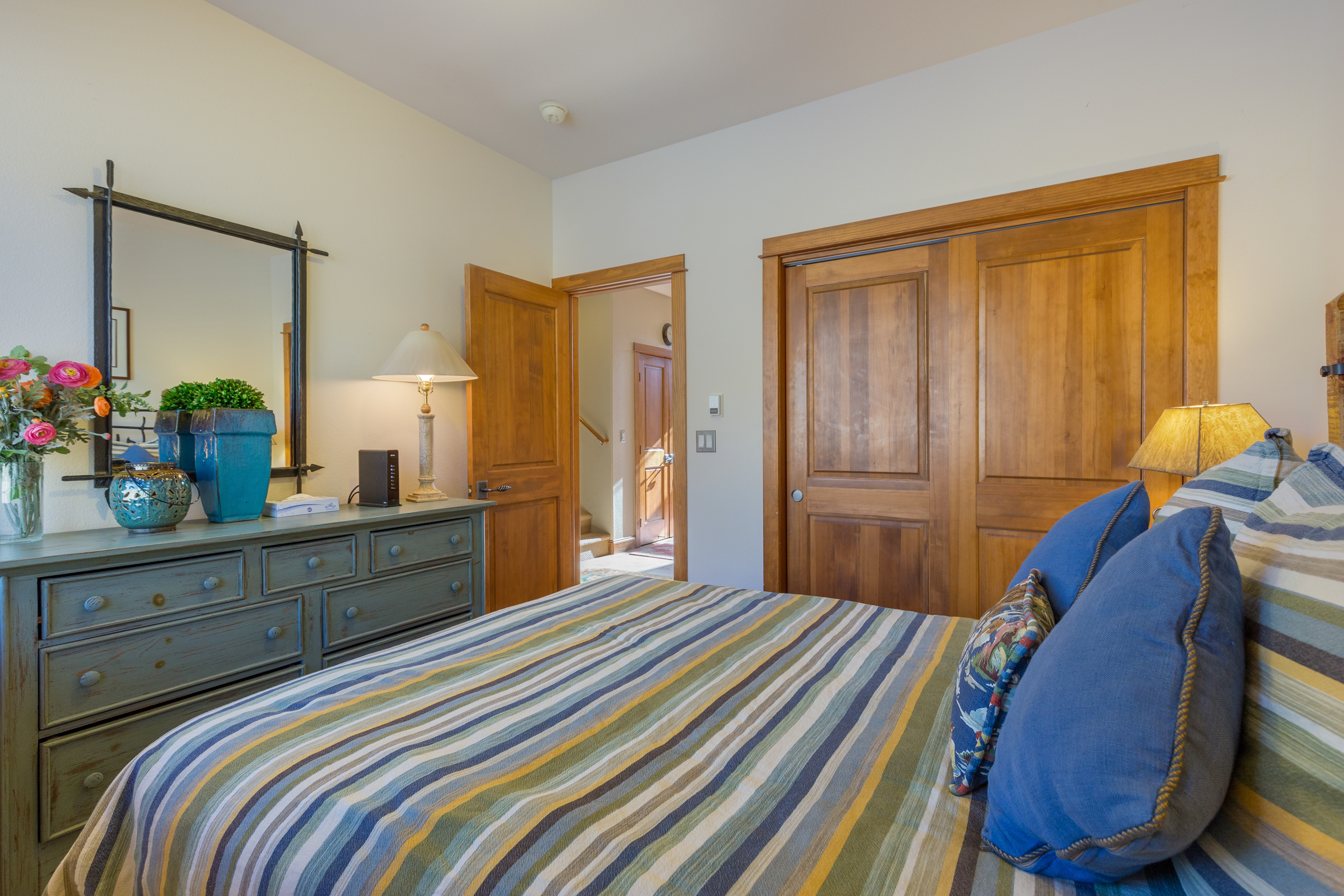 The first guest bedroom features a queen-sized bed.