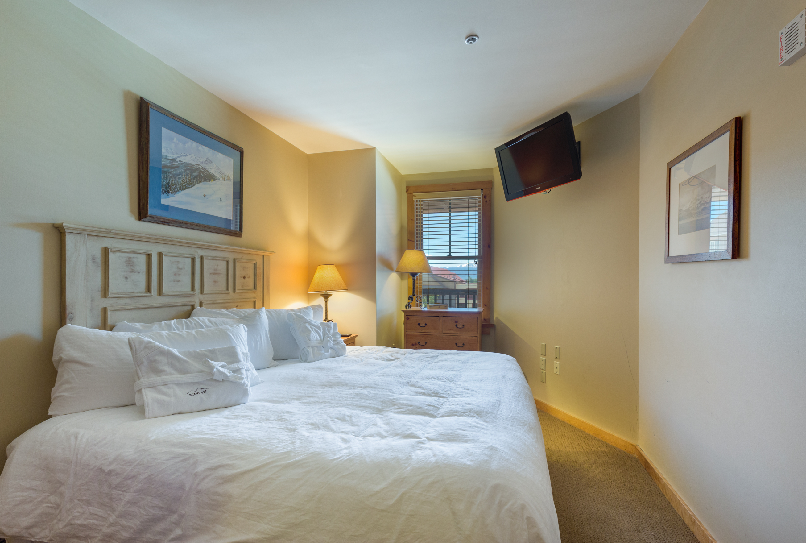 The second guest bedroom features a king-sized bed with Ivory White Bedding and a flat screen TV.