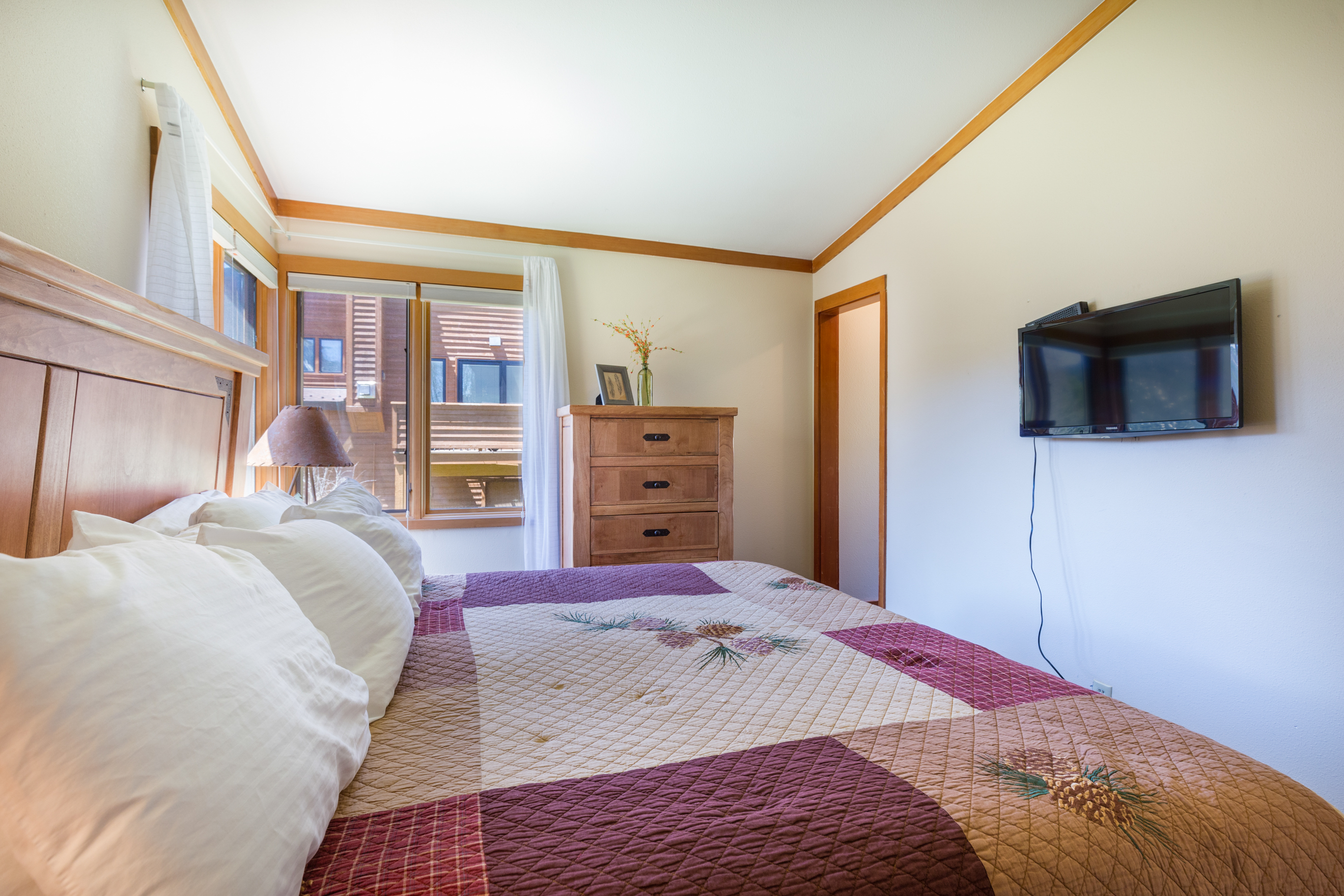 The first guest bedroom features a queen-sized bed and a mounted flat screenTV.