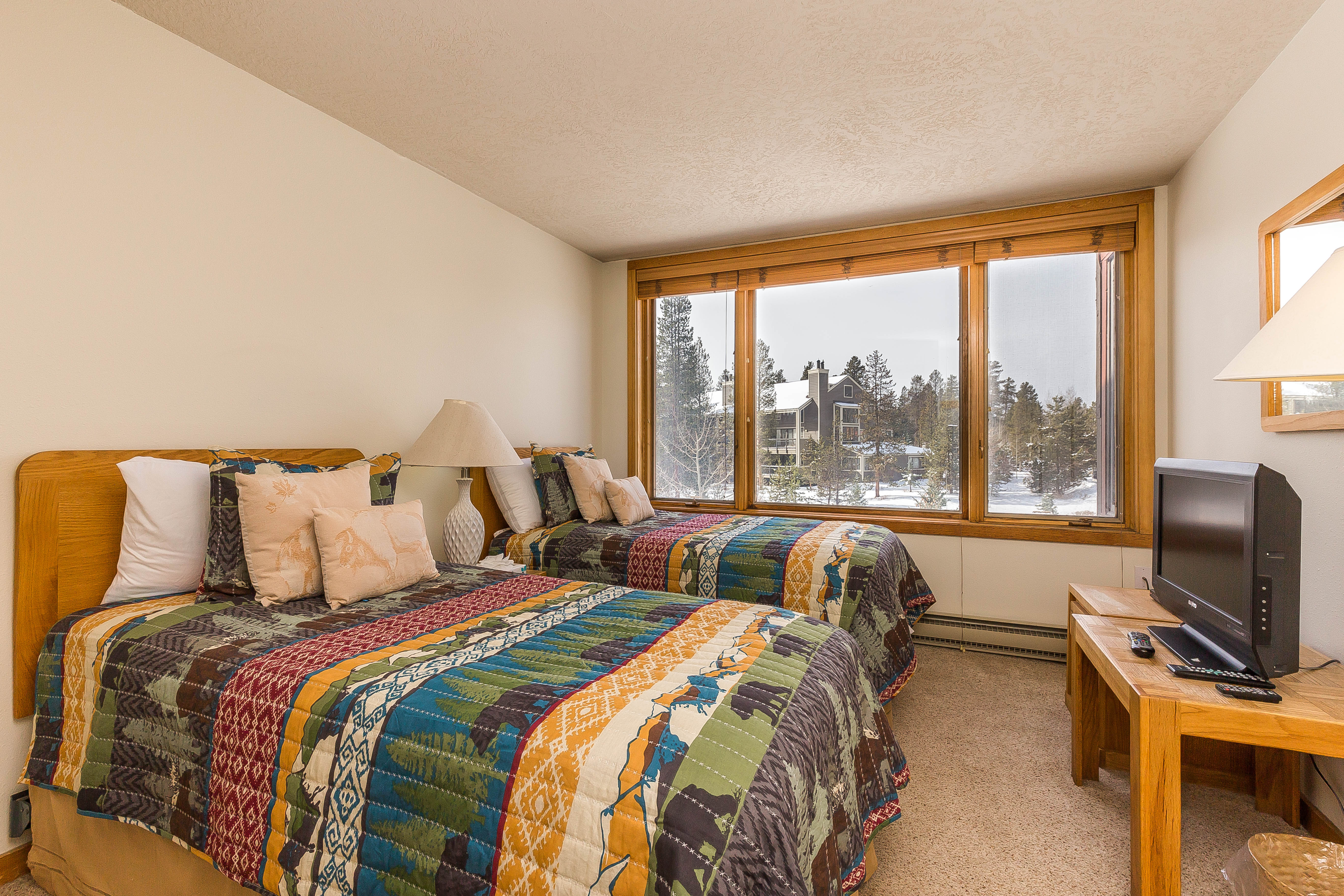 The guest bedroom features two twin-sized beds, a flat screen TV and beautiful views through the picture frame windows.