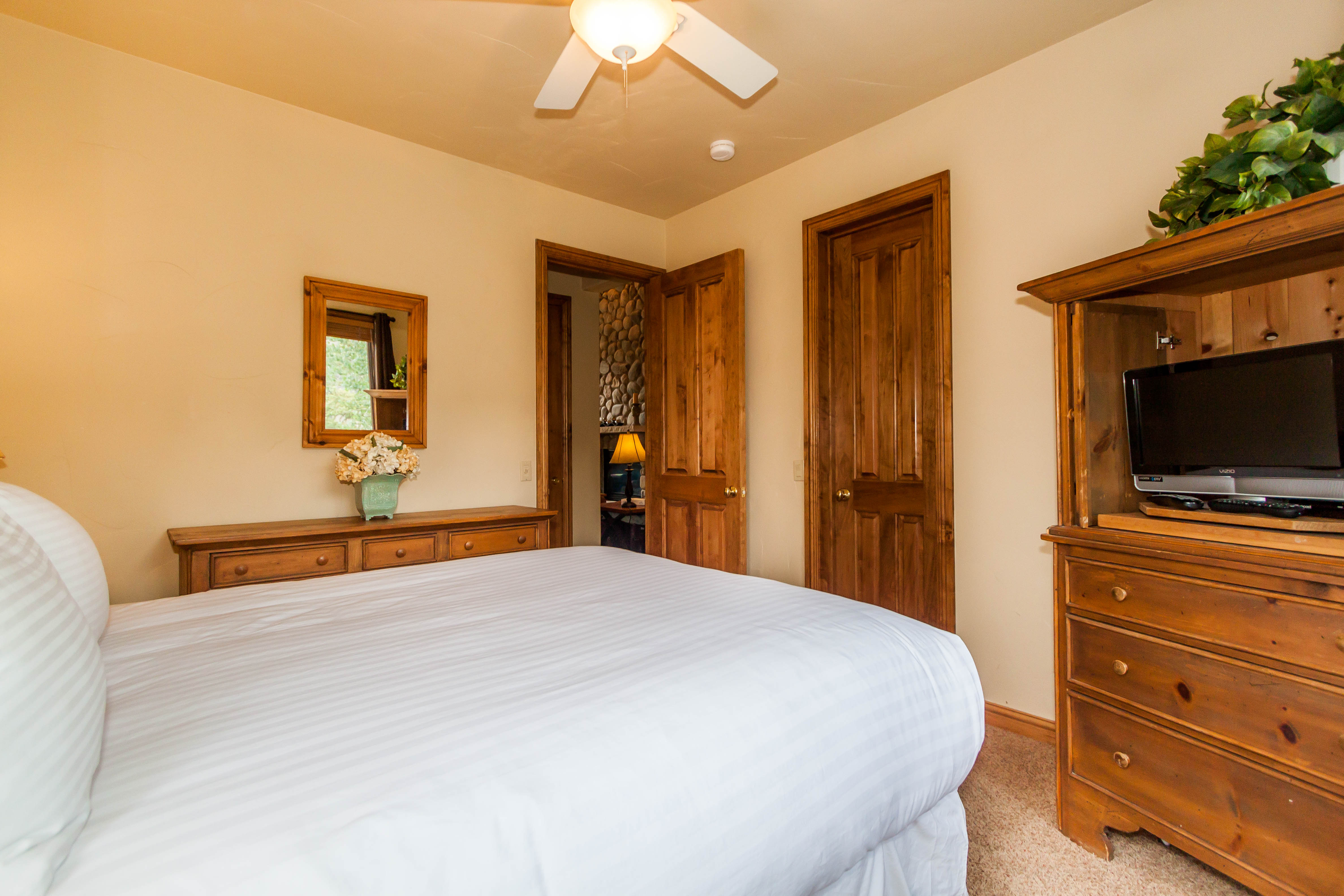 The first guest bedroom features a queen-sized bed with Ivory White Bedding and a flat screen TV.