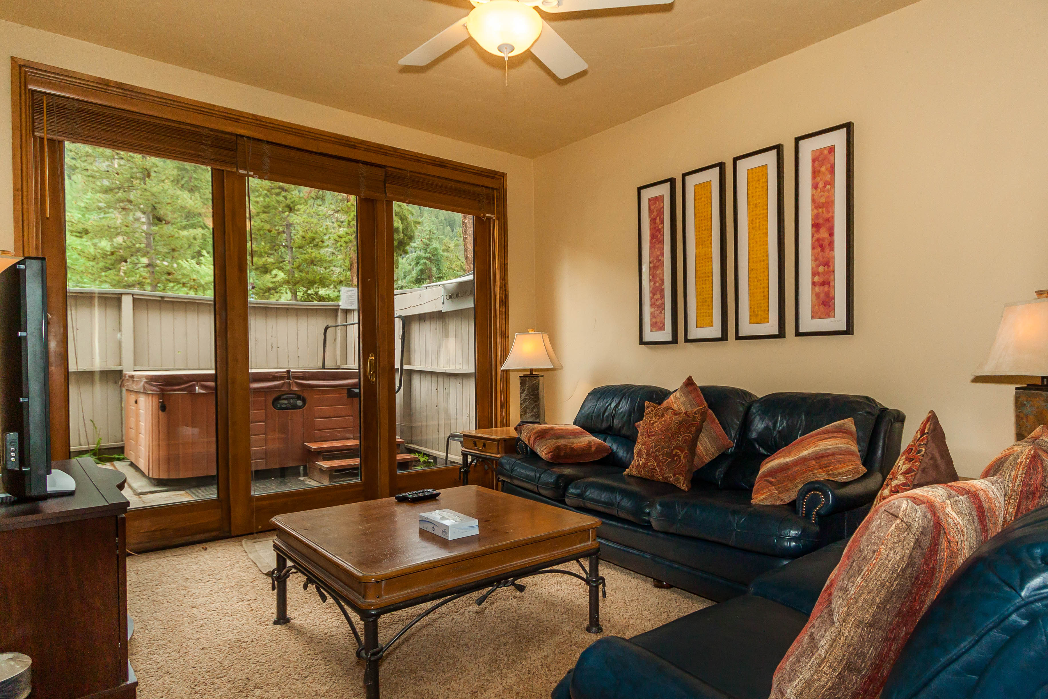 The den features comfortable seating, a flat screen TV and access to the partially covered patio with private hot tub.