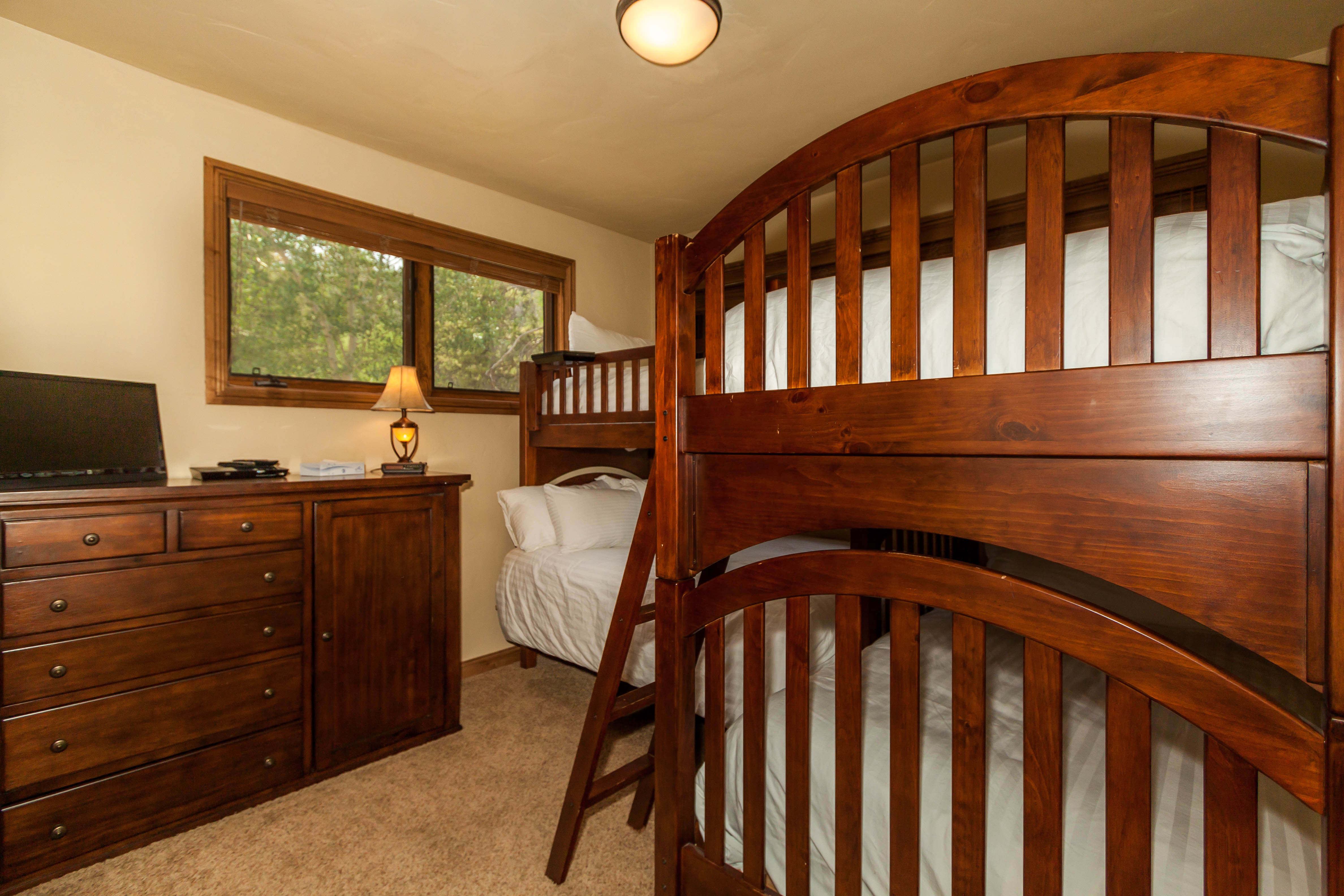 The second guest bedroom features two sets of bunk beds with Ivory White Bedding and a flat screen TV.