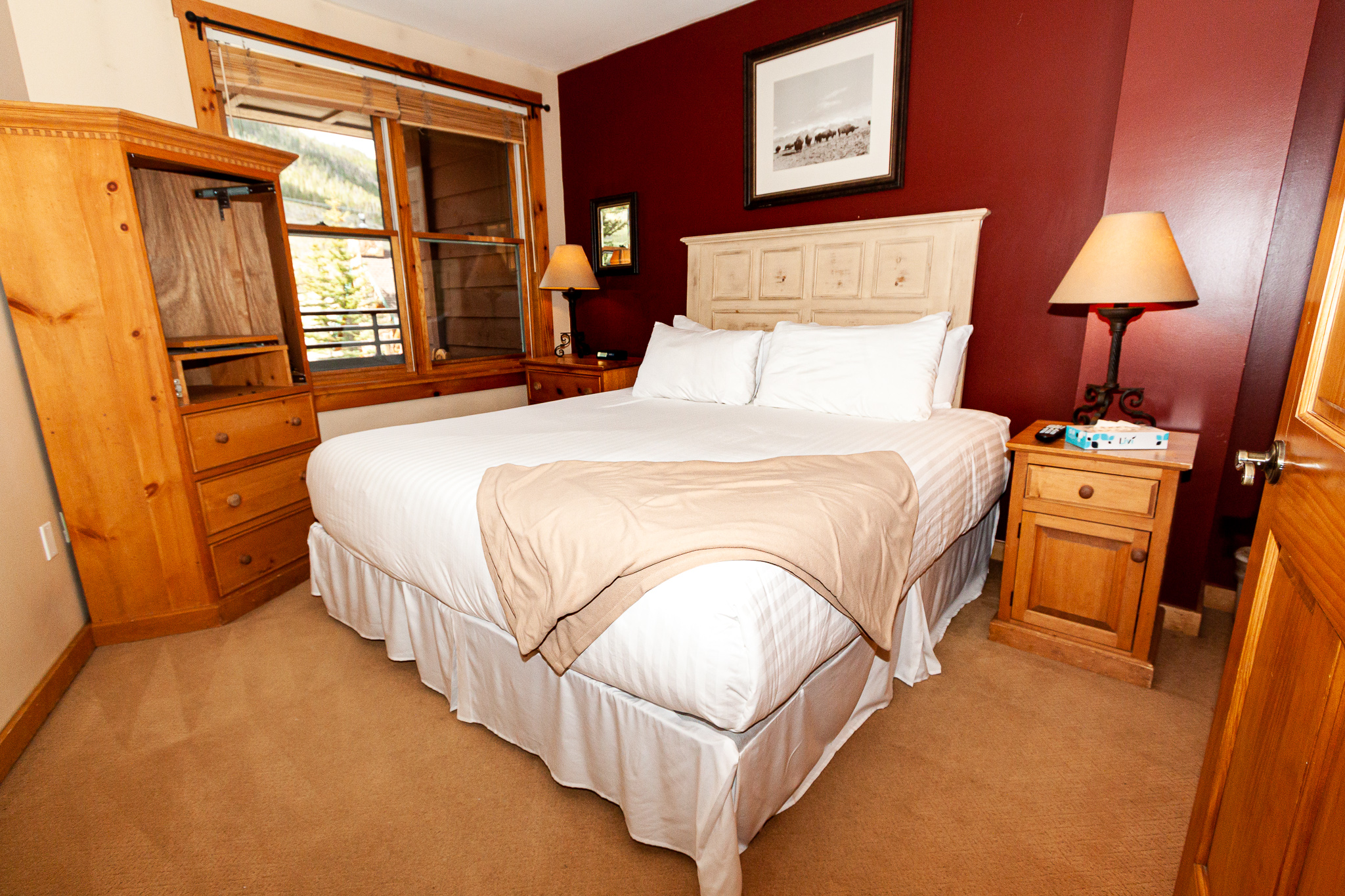 The bedroom features a king-sized bed and a mounted flat screen TV. **New photo coming soon.**