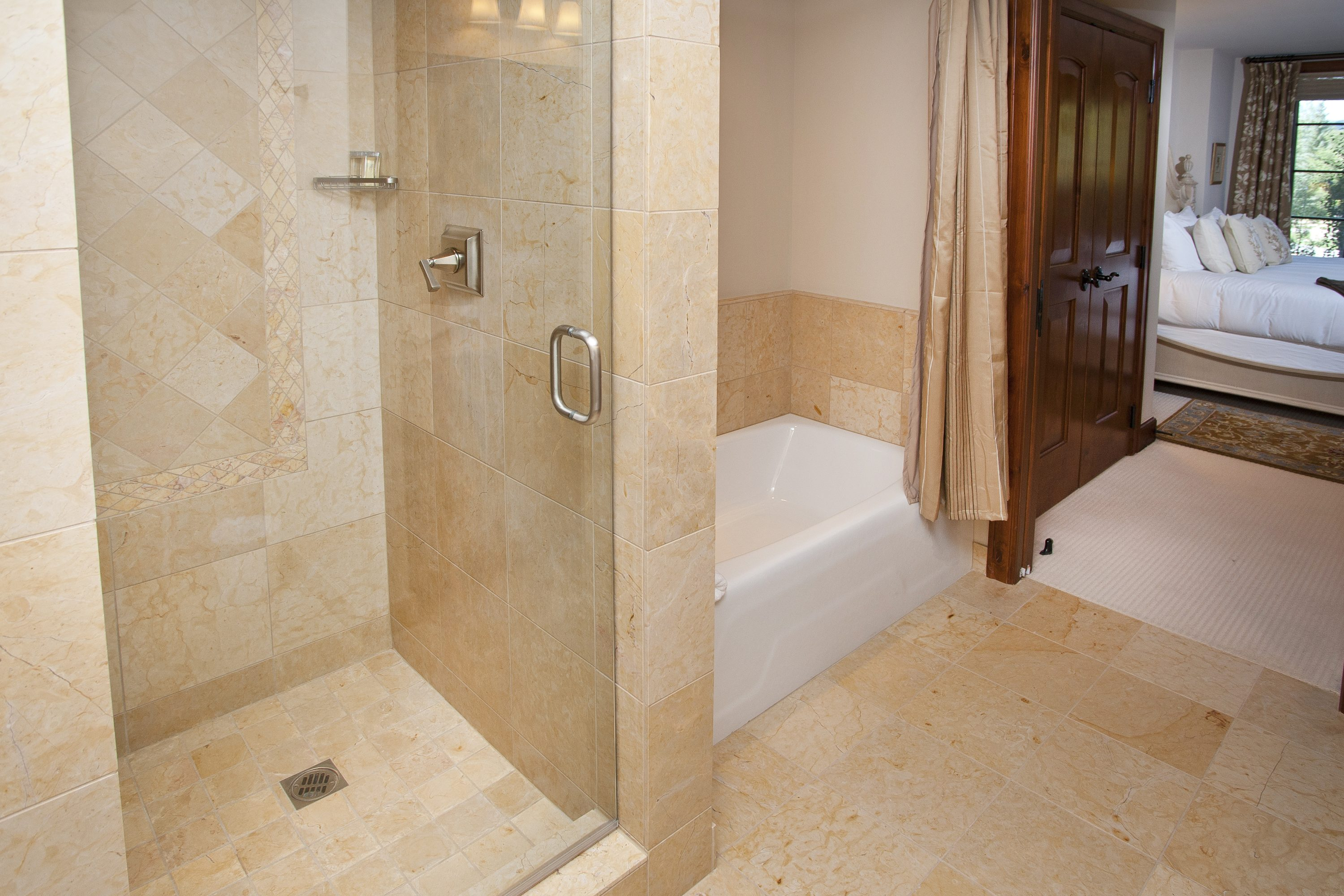 Beautiful marble bathroom with tub and walk in shower, nice towels, toiletries