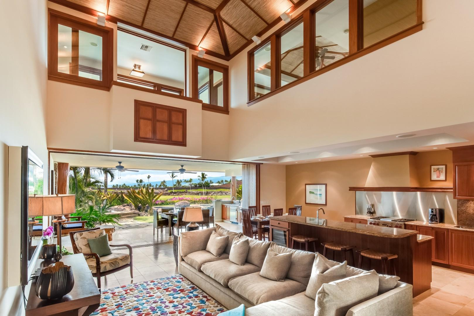 Spacious & Elegantly Appointed Living Room w/ Vaulted Ceilings & Electronic Pocket Doors that Open to Lanai and Pool Area
