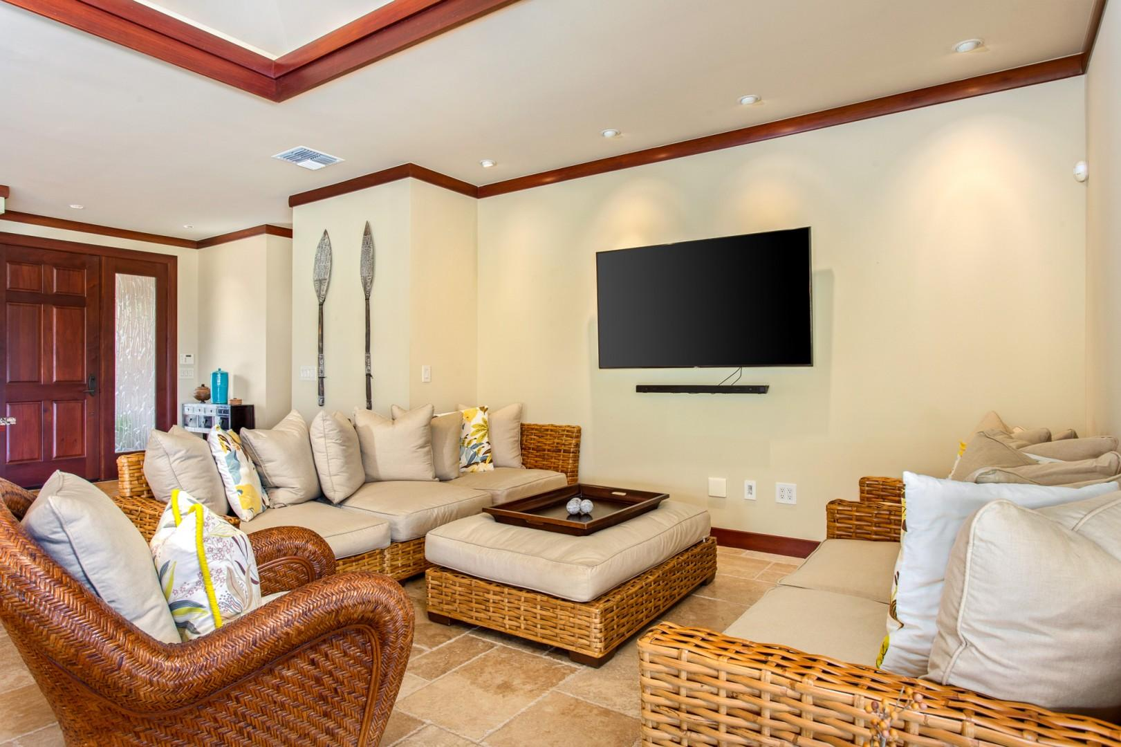 """Recessed lighting, plush seating and a 65"""" wall mounted flat-screen """"smart"""" cable television in the living area."""