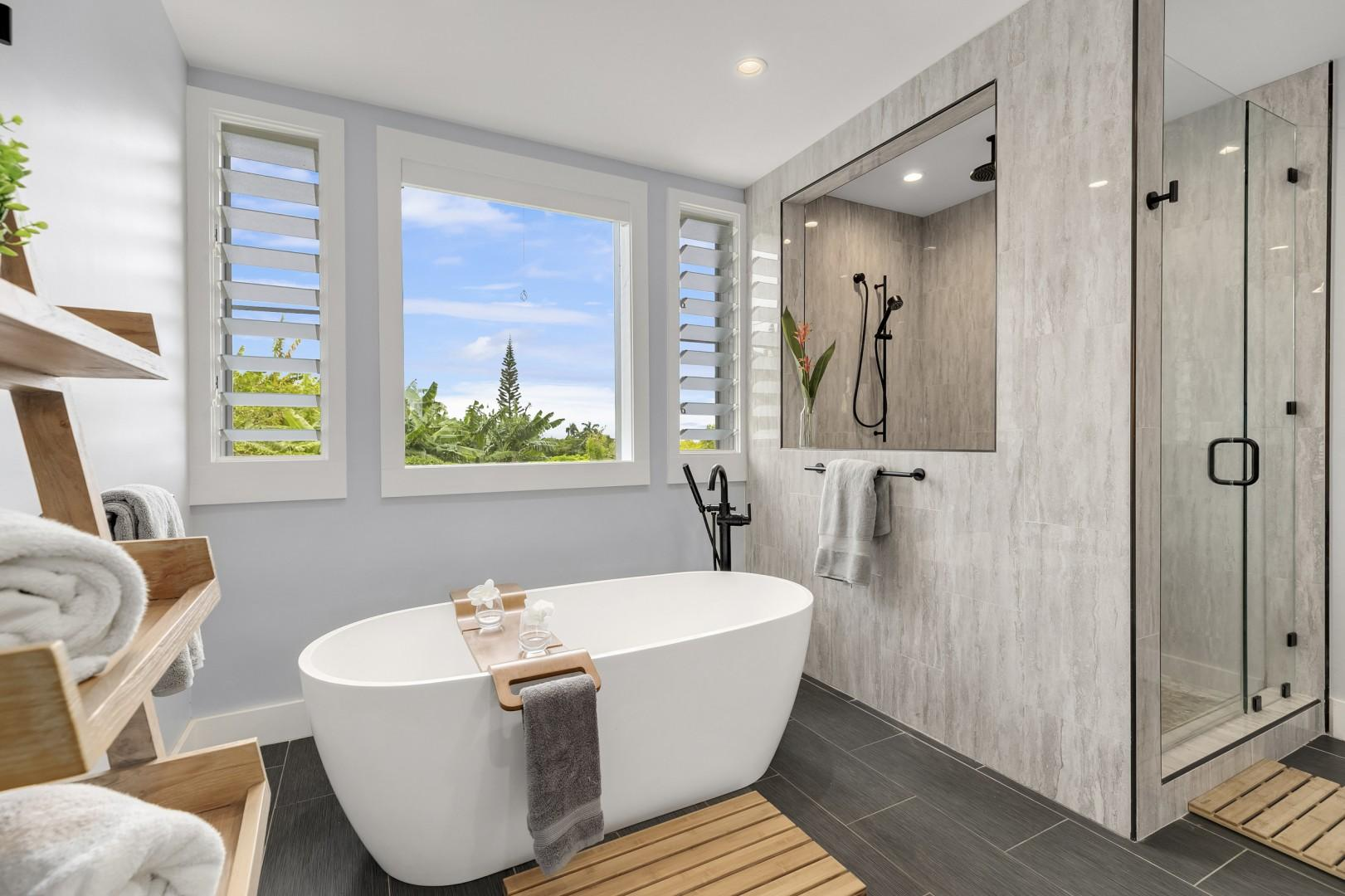 Master bath with soaking tub, custom shower and views of the greenery outdoors.