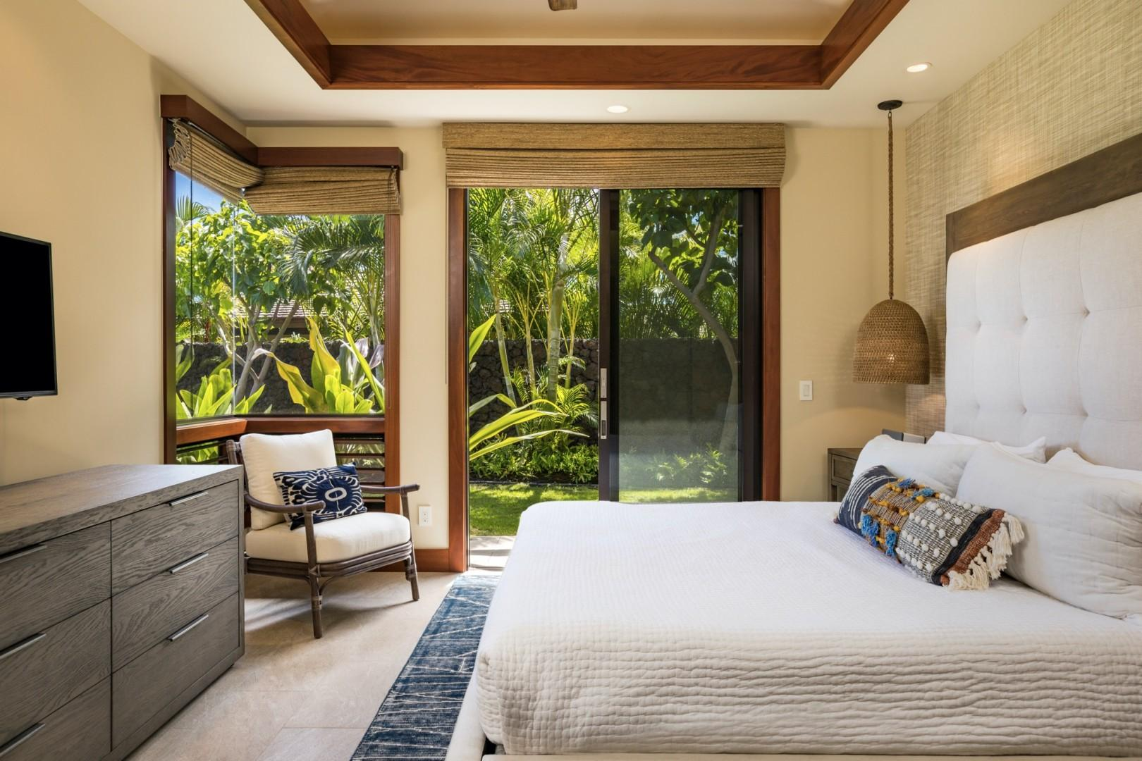 Guest bedroom two, off the kitchen, boasts sliding doors to a private lanai with lawn area.