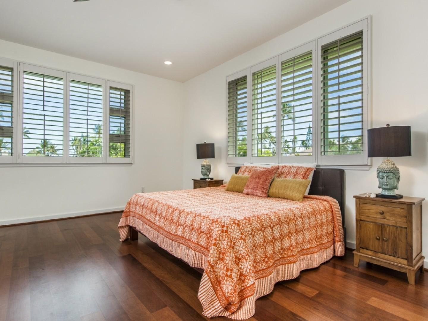Master suite with king-size bed and plantation shutters around all the windows.