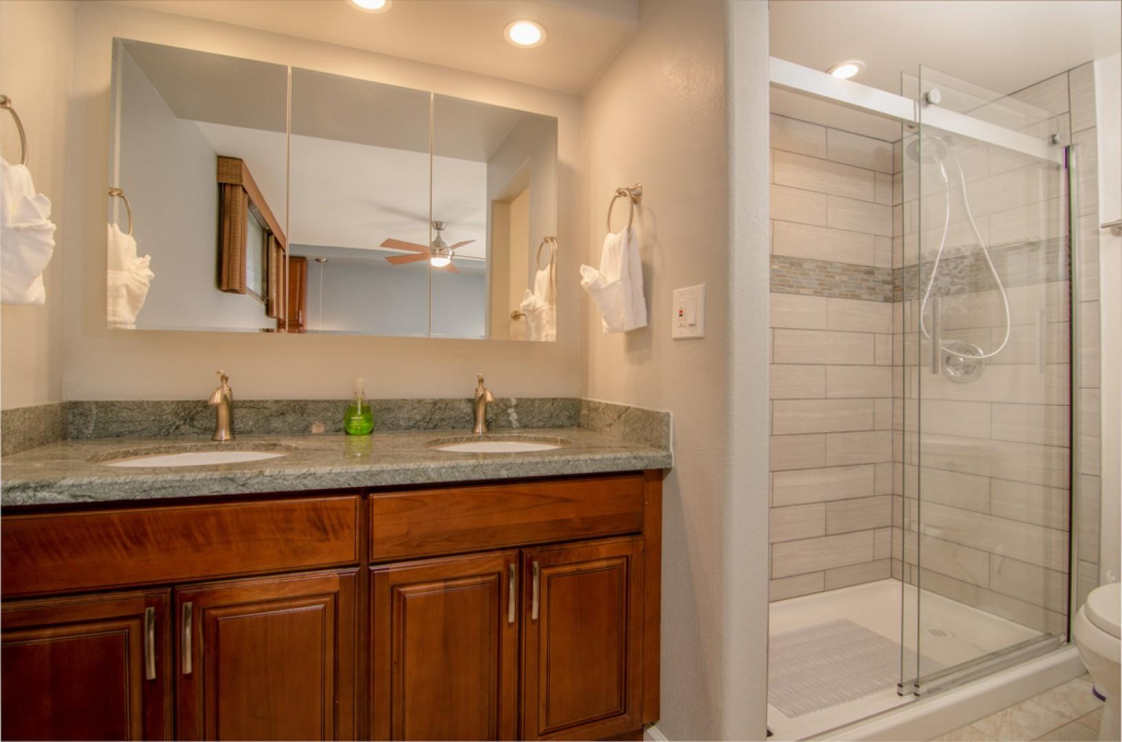 Guest bathroom includes his and hers sinks & a step in shower.