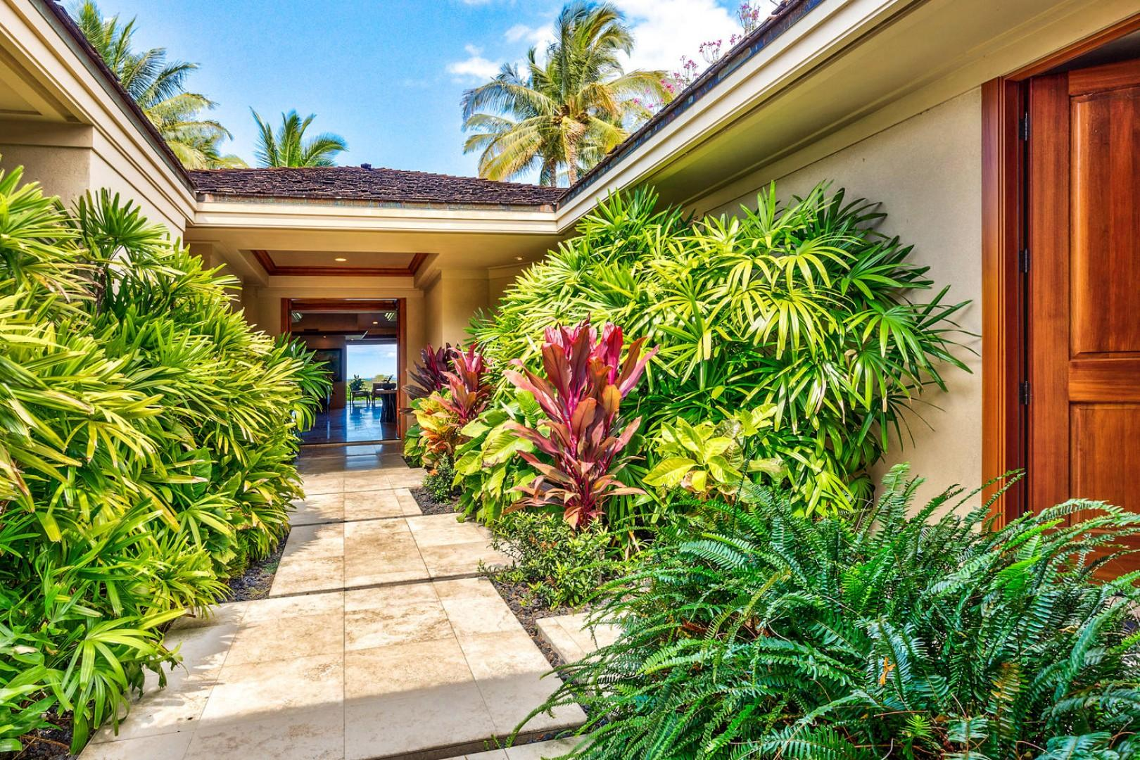 Private entryway with lush tropical landscaping.