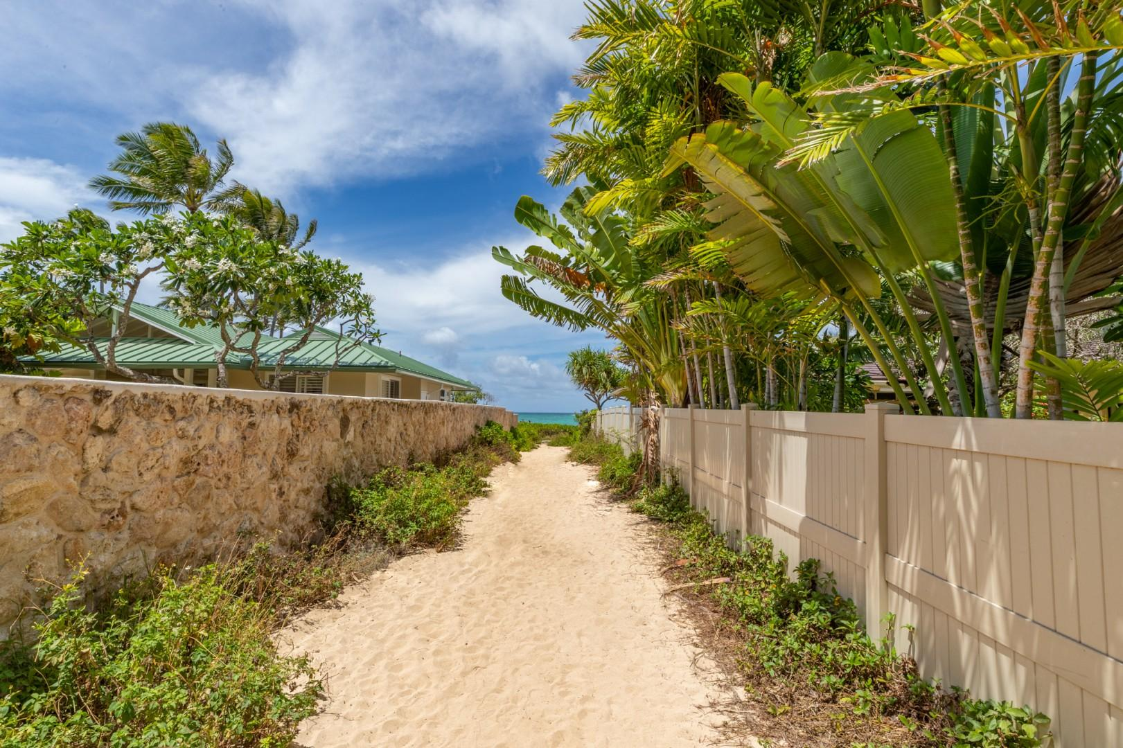 The sandy path leads to turquoise waters