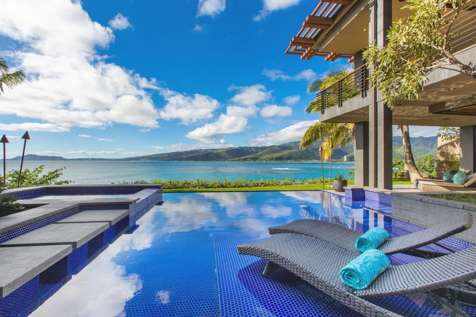 Infinity pool with chaise lounge chairs.