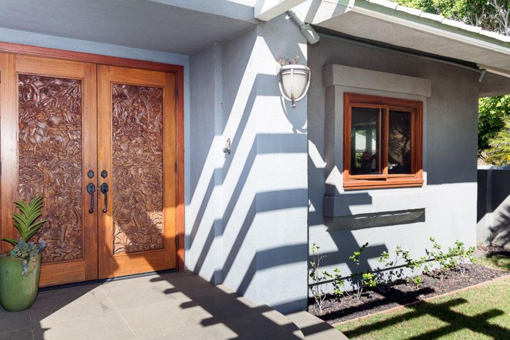Beautifully hand carved door welcomes you inside this home