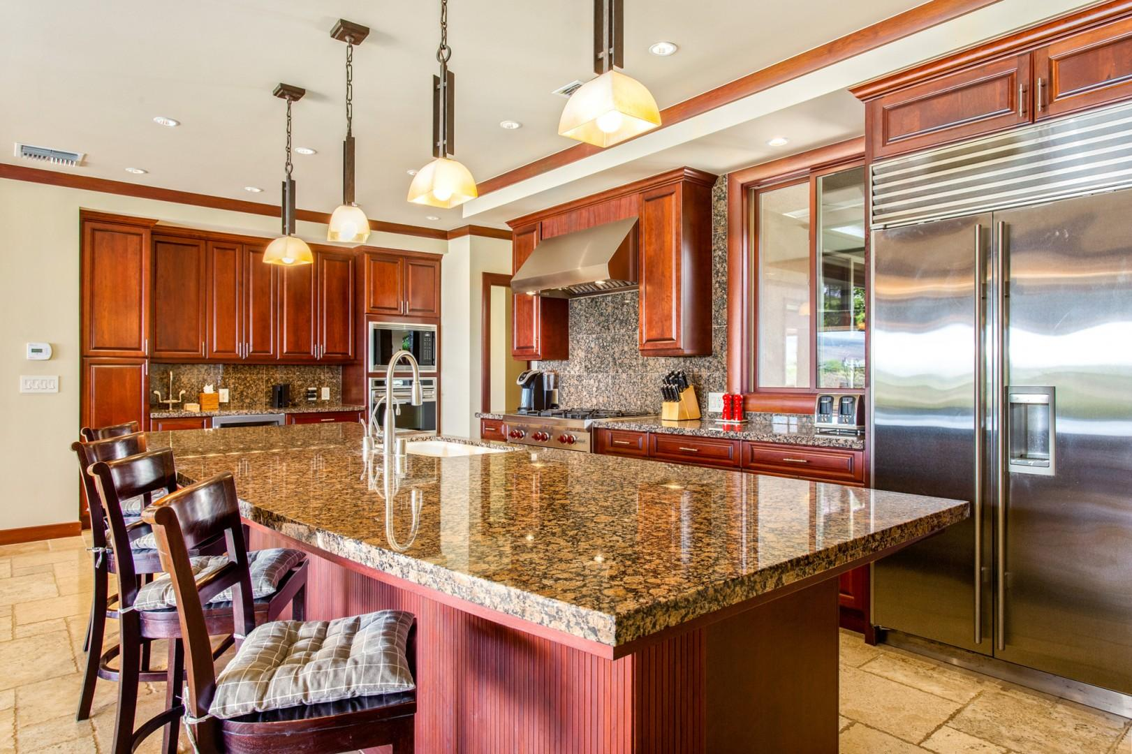 Alternate view of kitchen showcasing spacious layout, bar seating and chic recessed lighting.