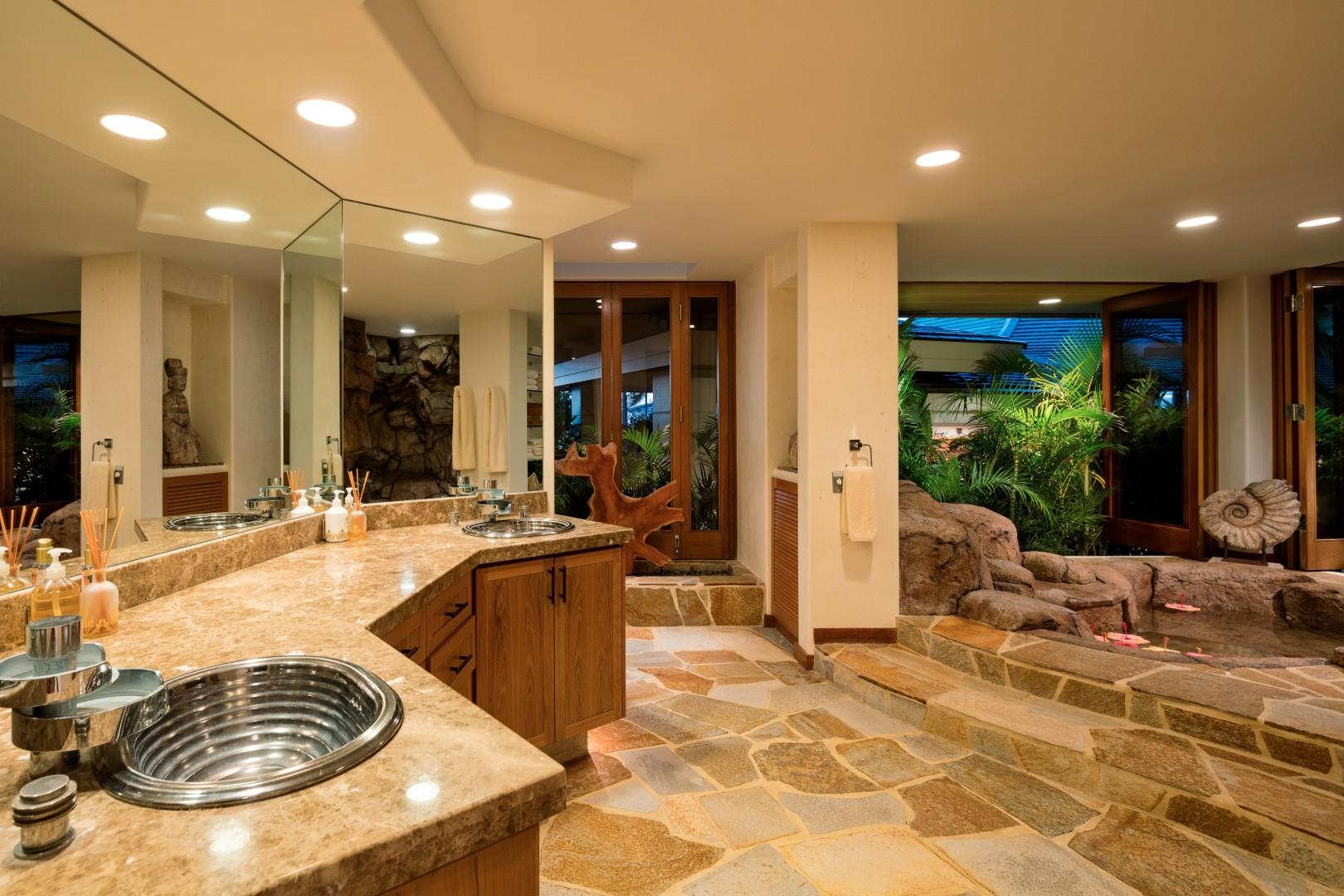 Palatial master bath with dual vanity, fabulous rock soaking tub, walk-in shower, and privacy commode.