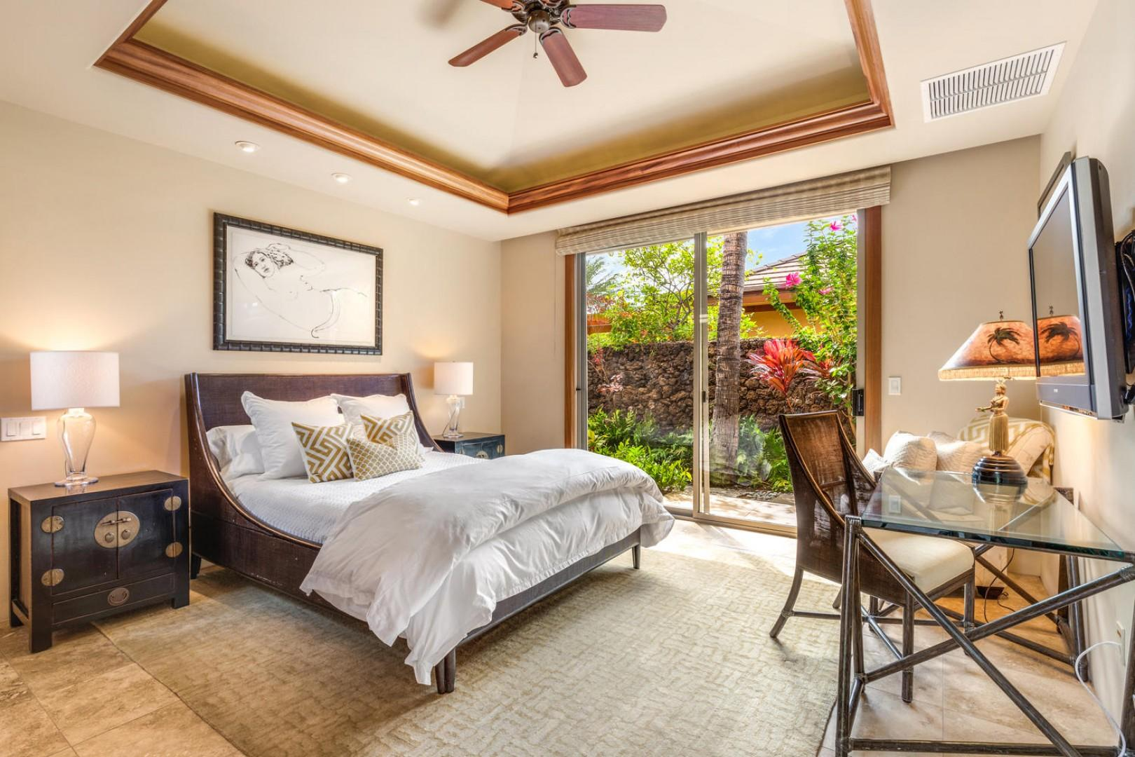 First guest suite with queen bed, wall-mounted flat screen television, sliding doors to outdoor living and en-suite bath.