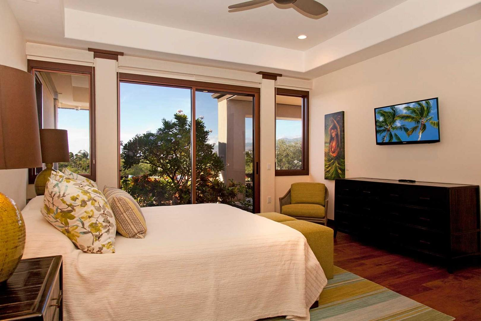 Third bedroom, with king bed, flat-screen TV, walk-in closet, en suite bath, and sliding doors to pool deck.