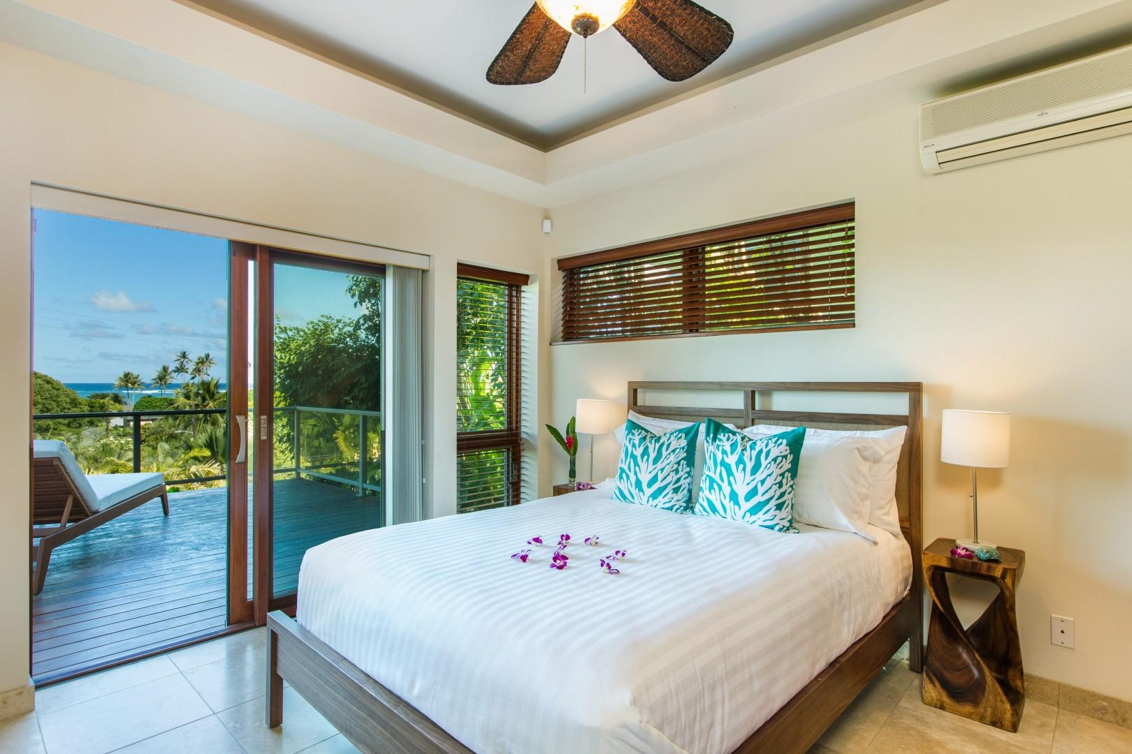 First floor queen bedroom with sliding doors leading to an ocean-view lanai.