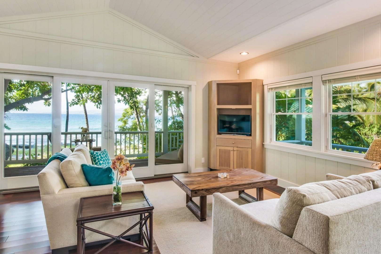 Ohana Guest Cottage Living Room w/ Split Air-Conditioning, Flat Guest Ohana Guest Cottage Living Room Furnished w/ Comfy Sofas and Queen Sleeper Sofa, Flat Screen Smart TV, Sliding Glass Doors to Private Lanai w/ Stunning Ocean and Garden Views