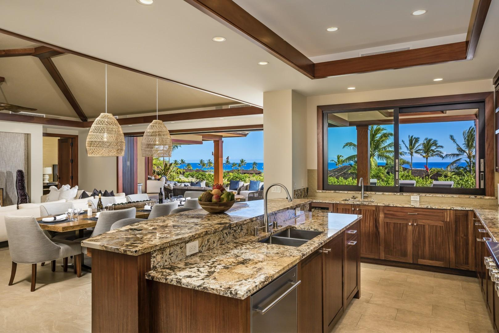 Stunning open concept kitchen with granite countertops, top tier appliances, two sinks, custom African mahogany cabinetry and a large pass through window to the outdoor BBQ area.