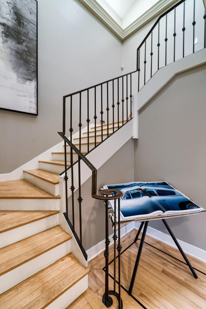 The main staircase leading to both master suites and bedroom 1, with two queen beds.