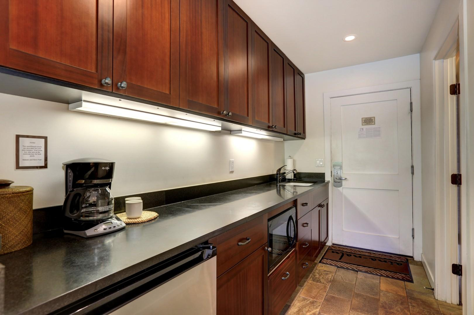 The kitchenette includes a mini refrigerator, a microwave, a coffee maker, a toaster, and a sink.