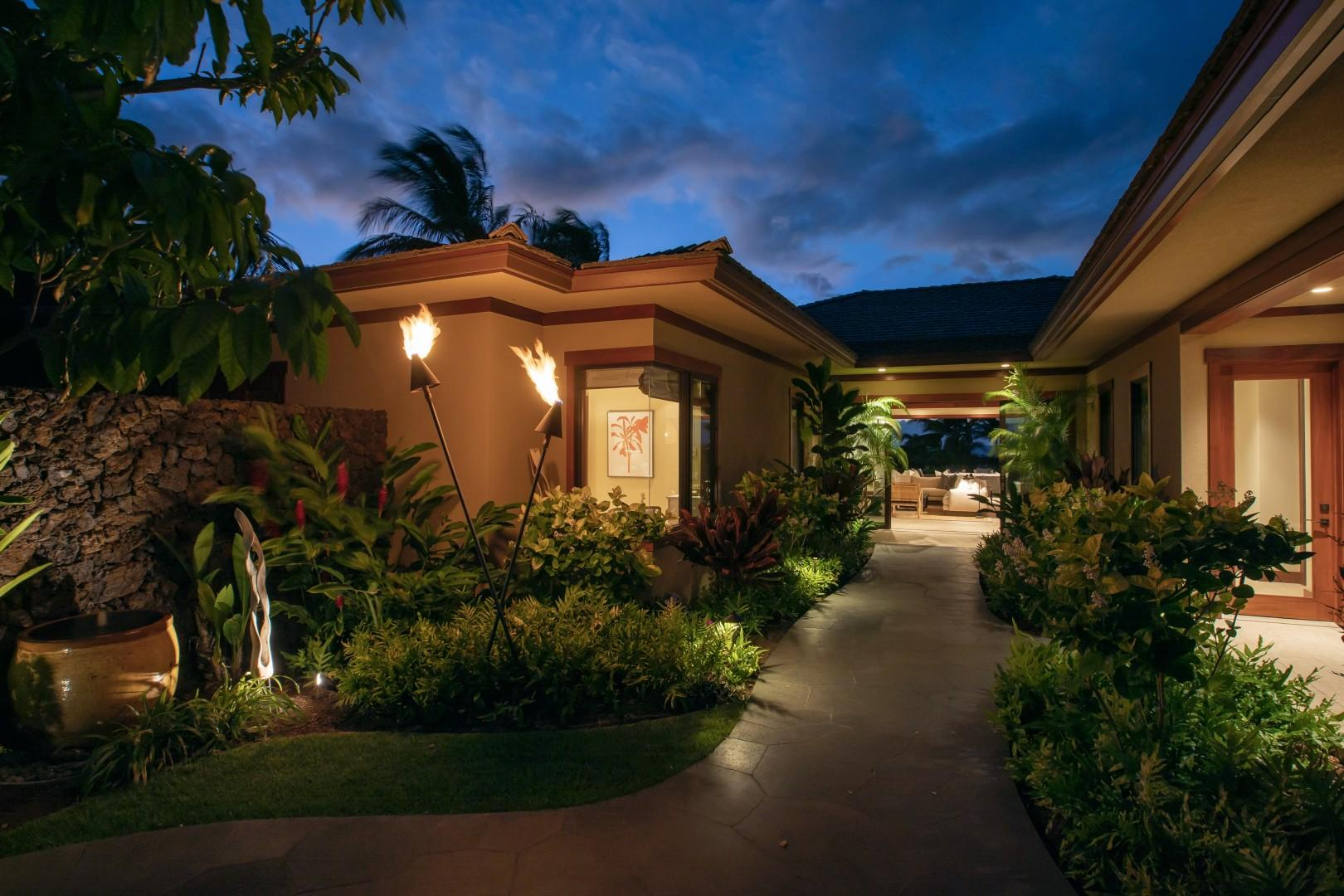 Front entryway at twilight with tiki torches lit.