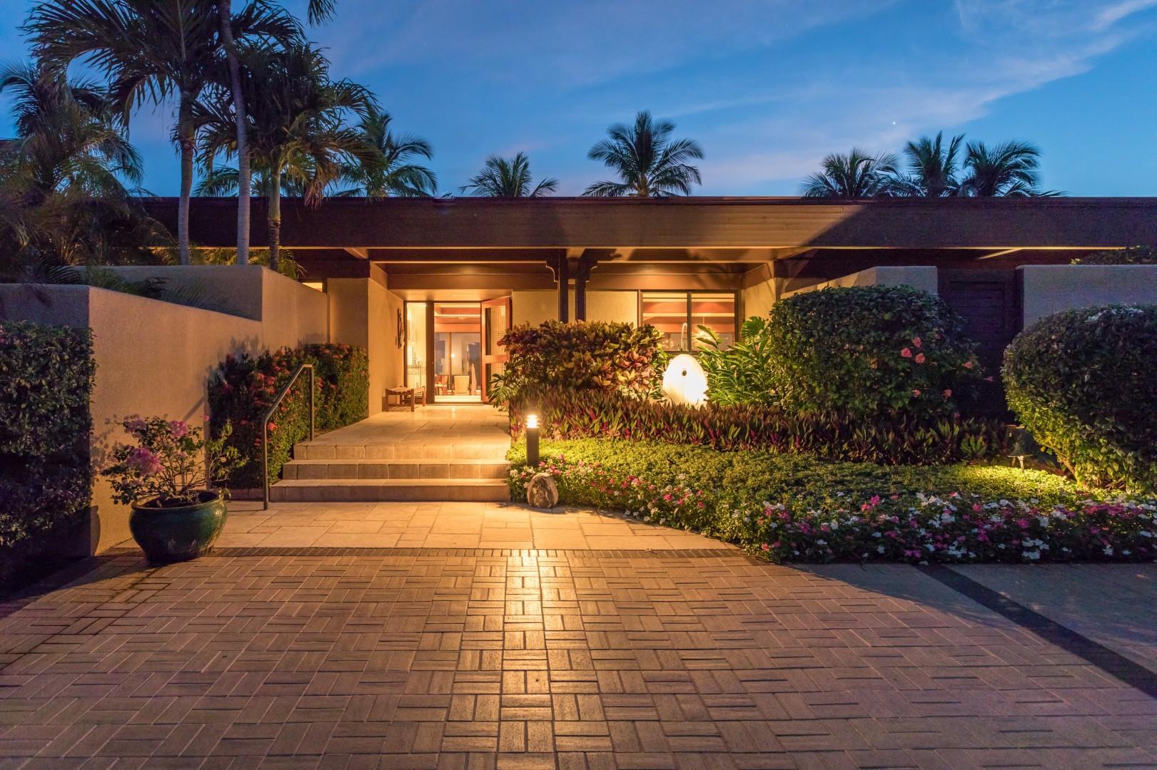 Regal entryway to villa at twilight.