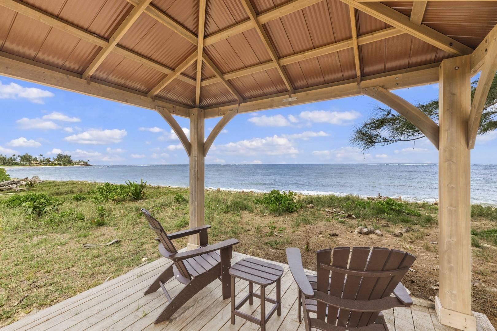 Beachfront gazebo for relaxing near the ocean.