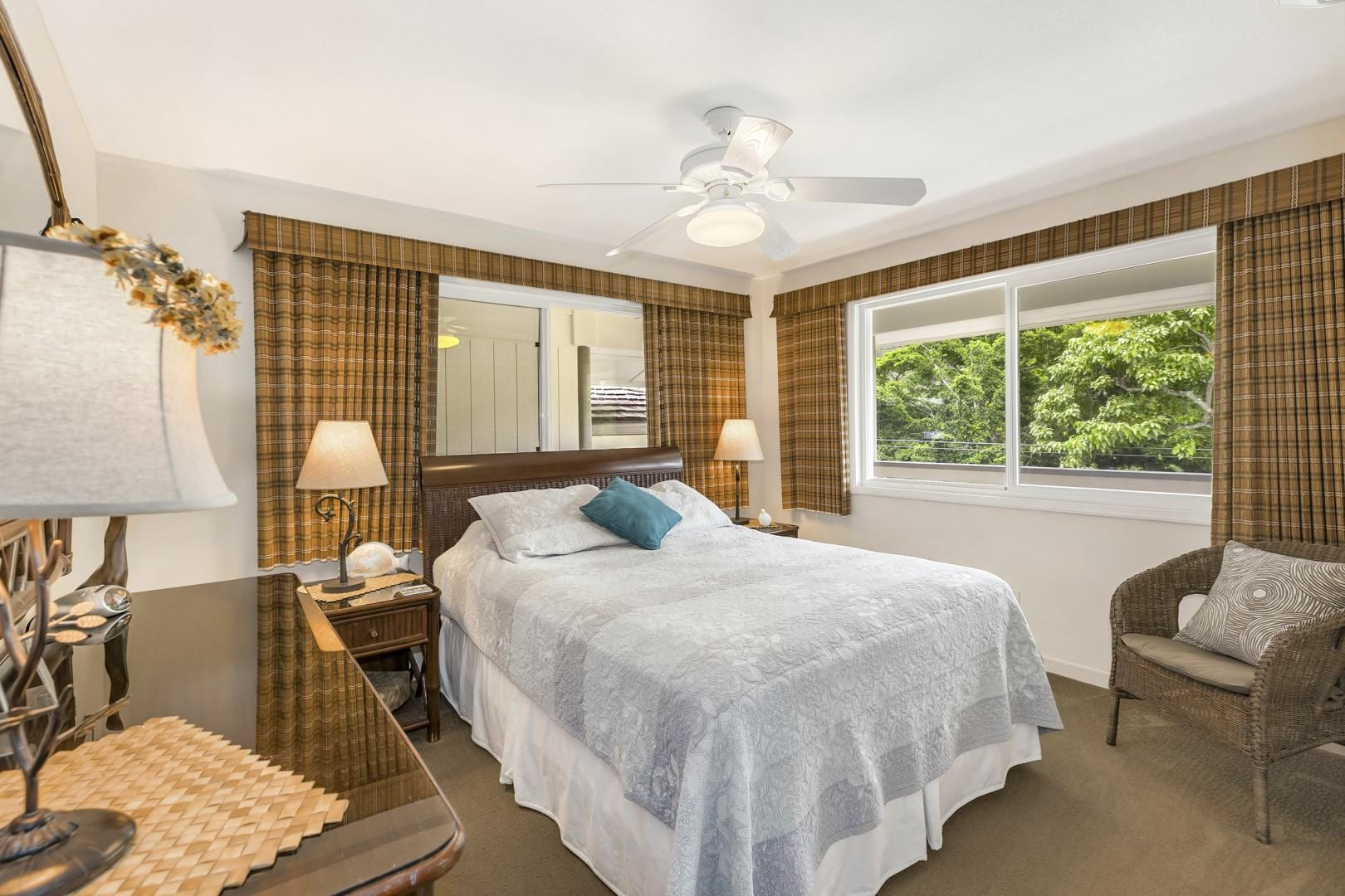 Guest bedroom upstairs with dresser and ceiling fan.