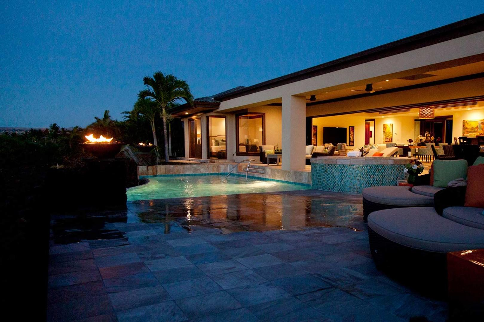 Evening shot of pool deck with view to covered lanai and interior of home.