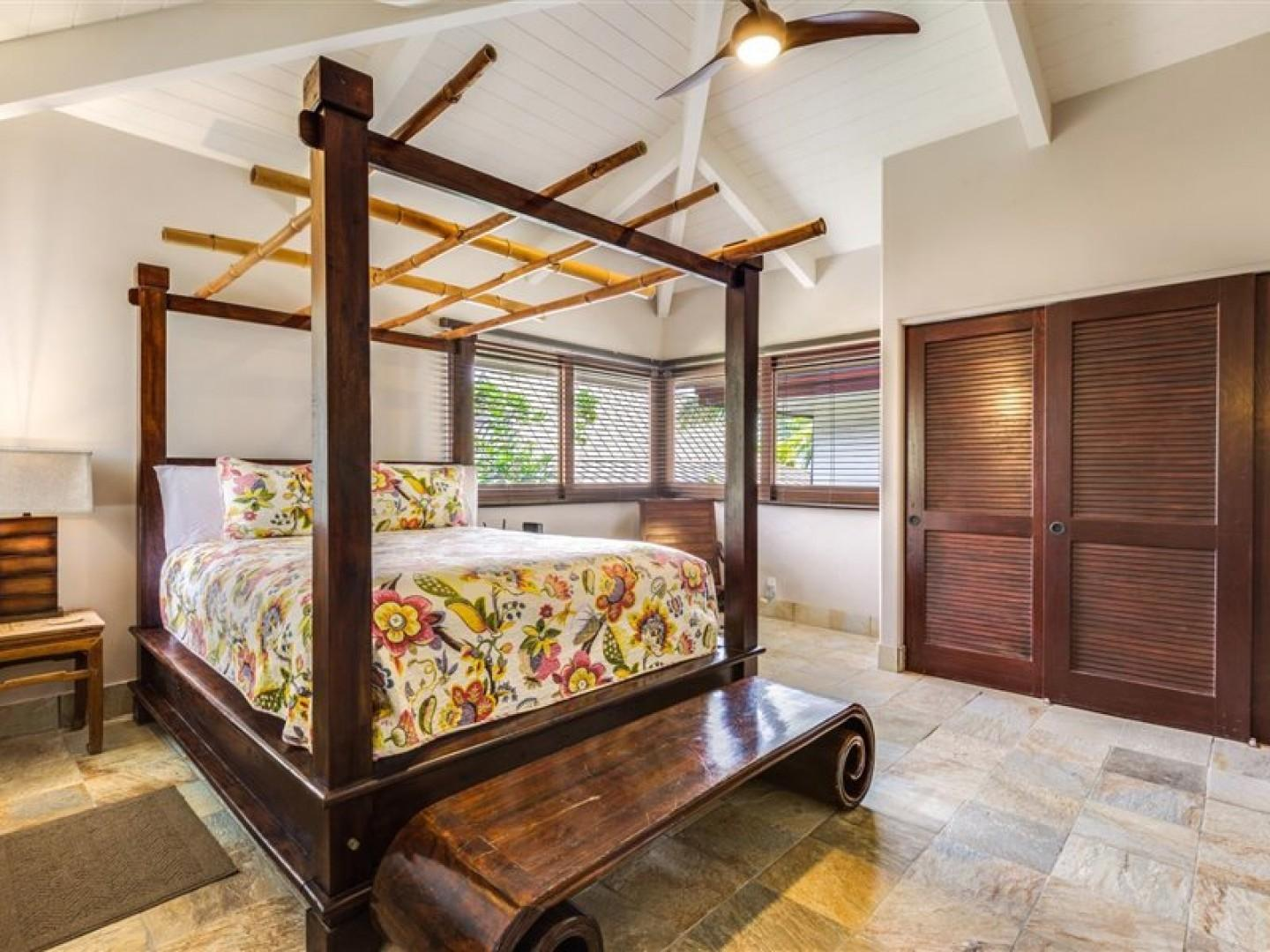 Guest bedroom with tropical touches and vaulted ceiling