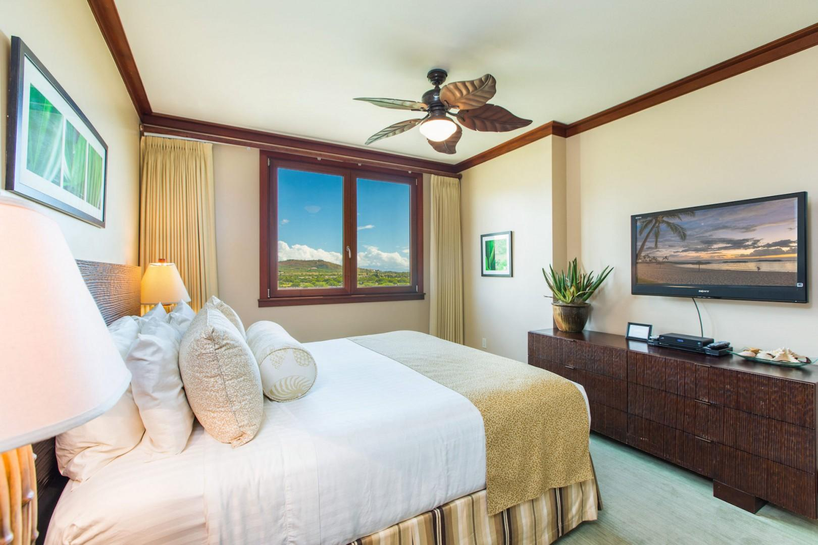 Master bedroom with king bed, wall mounted TV, ceiling fan, dresser, en suite bath; mountain and golf course views