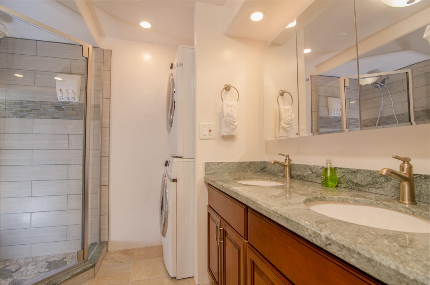 Lovely guest bathroom with large washer and dryer.