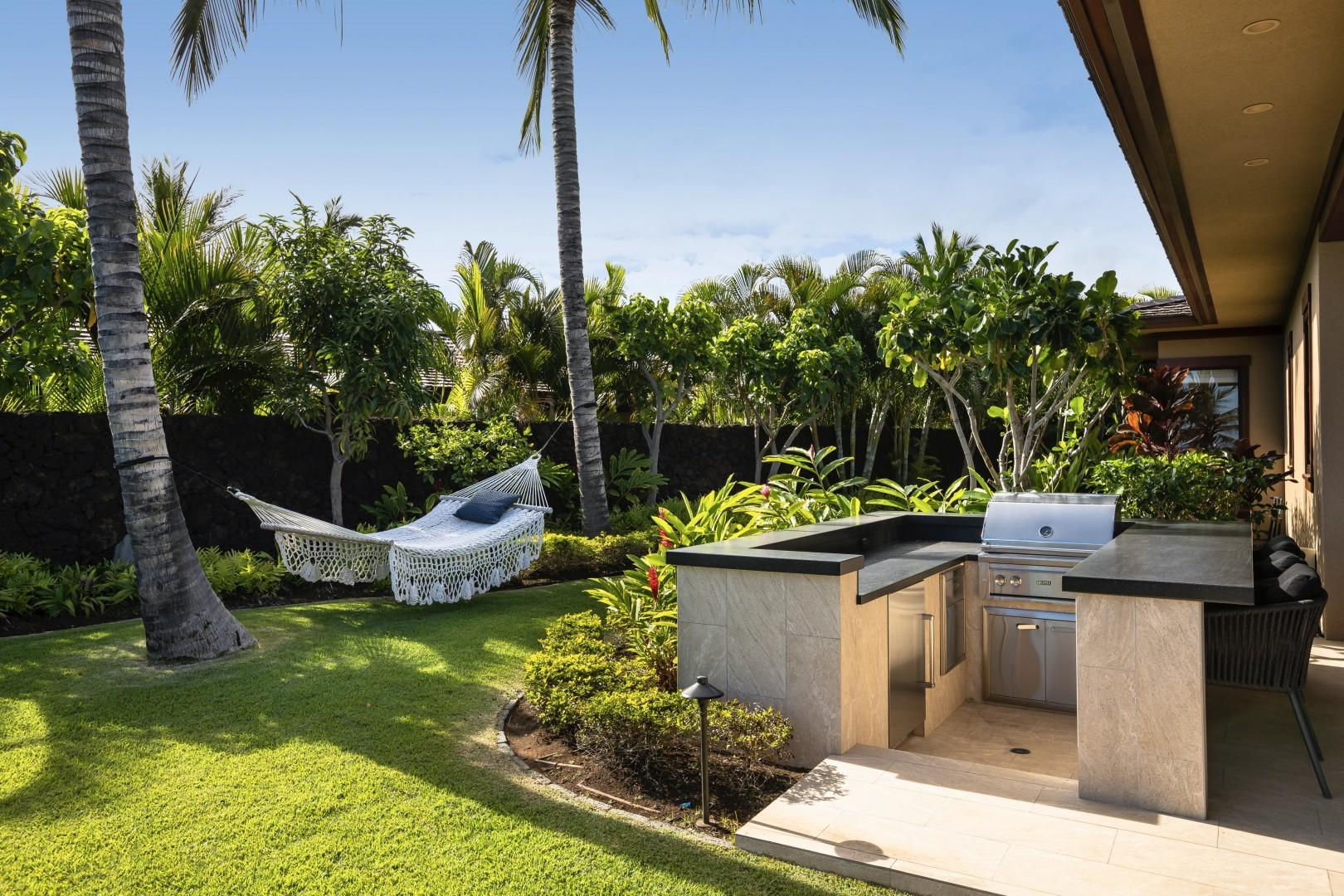BBQ grill area with ample prep space and mini fridge, with grassy private yard and hammock beyond.