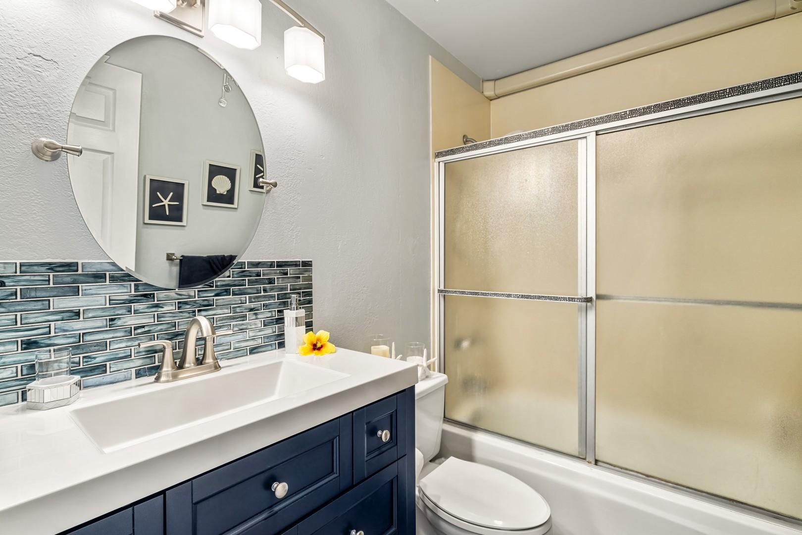 Detached guest bathroom with modern touches and tub shower combo