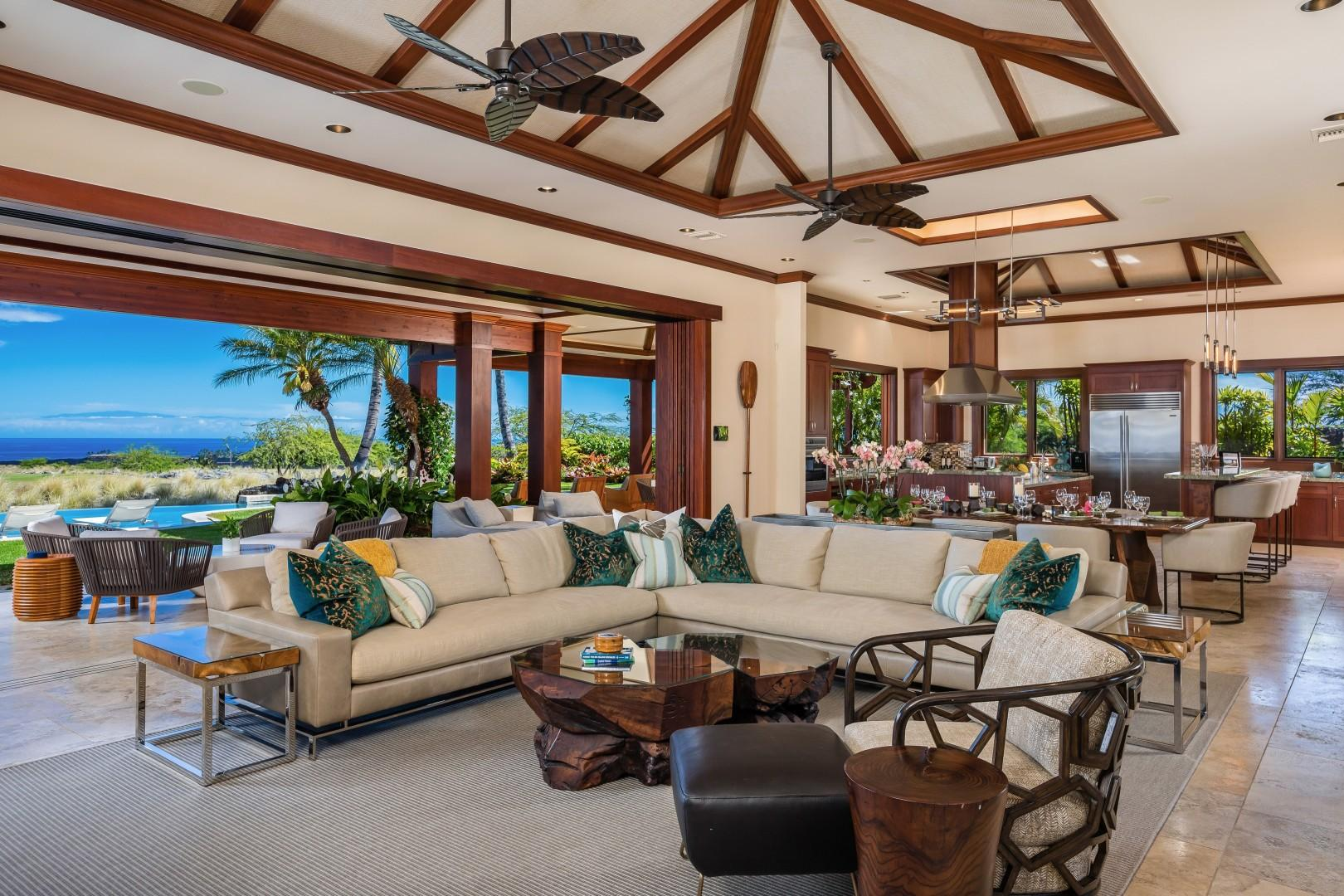 Spacious great room with vaulted ceilings and automated glass pocket doors to the lanai & pool deck, for luxurious Hawaiian indoor/outdoor living.