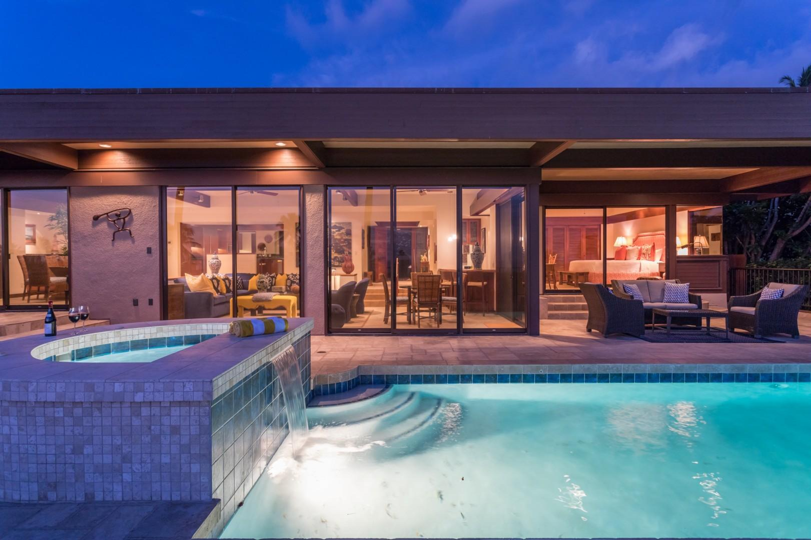 Waterfall jacuzzi at sunset, looking back through sliding glass doors to warmly lit home.