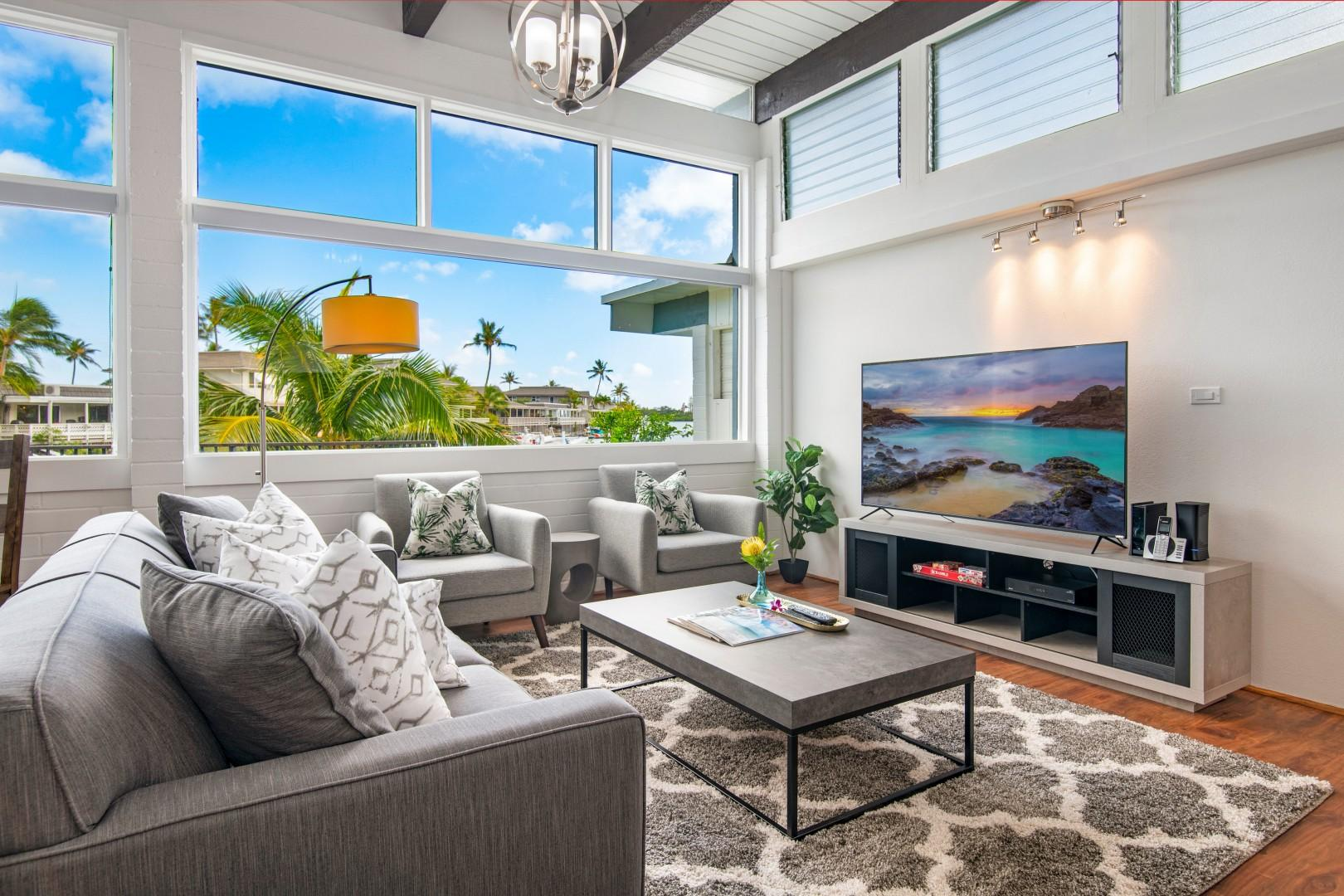 Open floor plan living room with large tv and marina views! (Living room includes a sleeper sofa.)