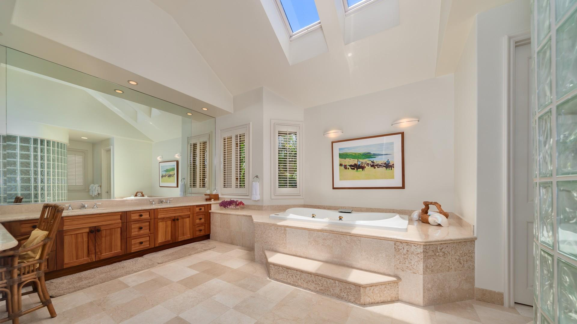 The large master bath is outfitted with dual sinks, a soaking tub, and a vanity area.
