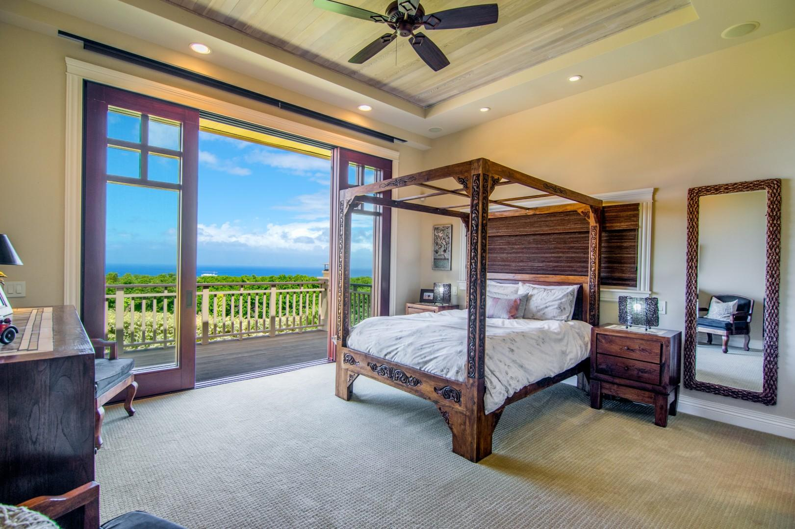 Guest Bedroom with Canopied Bed and Doors that Open to Bring in the Outside and View of the Ocean with En Suite Bathroom
