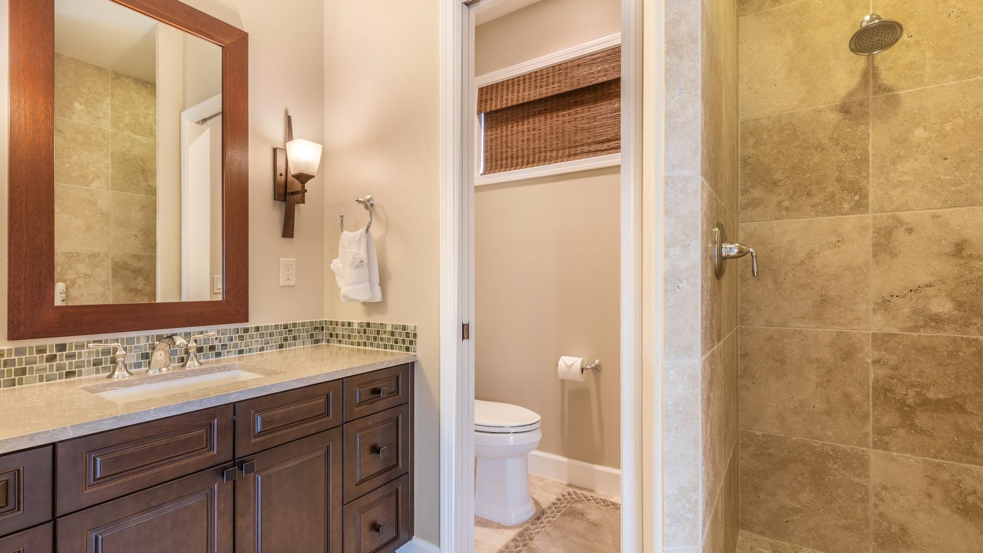 Fourth bath, with sandstone tiles and ocean-toned backsplash.